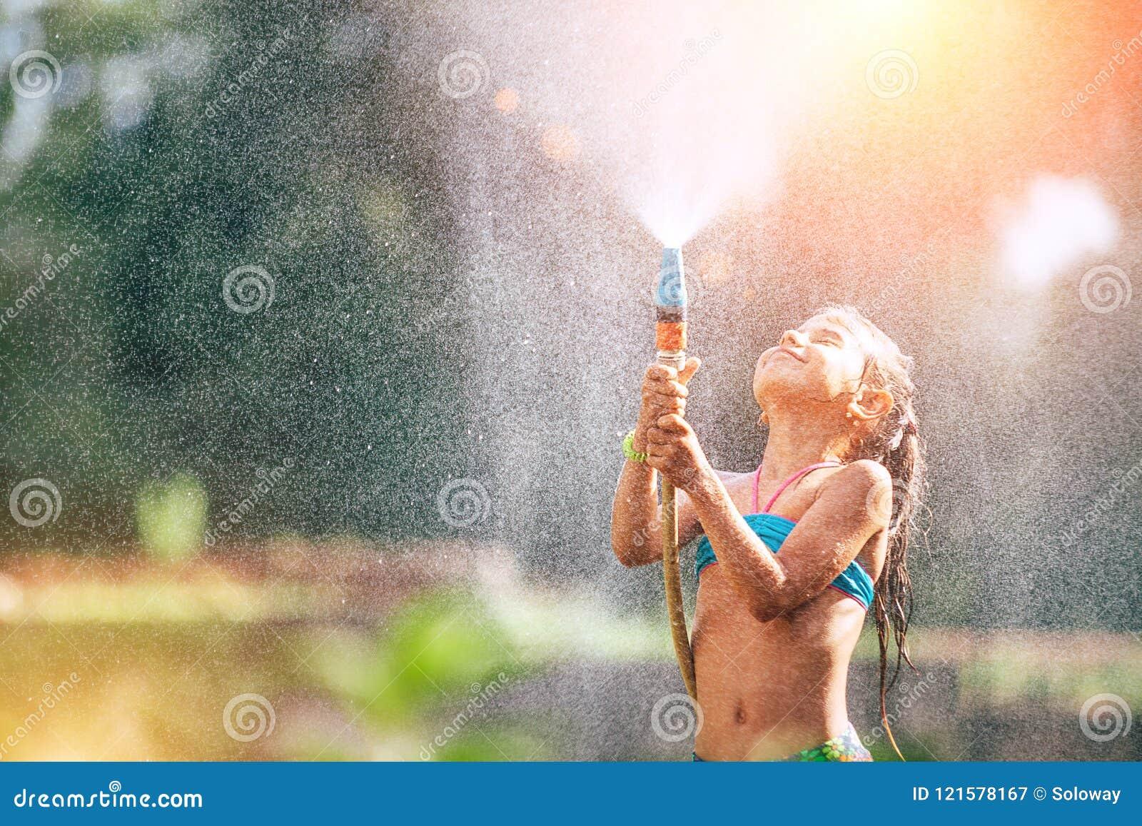 A menina bonito derrama-se da mangueira, faz uma chuva quente