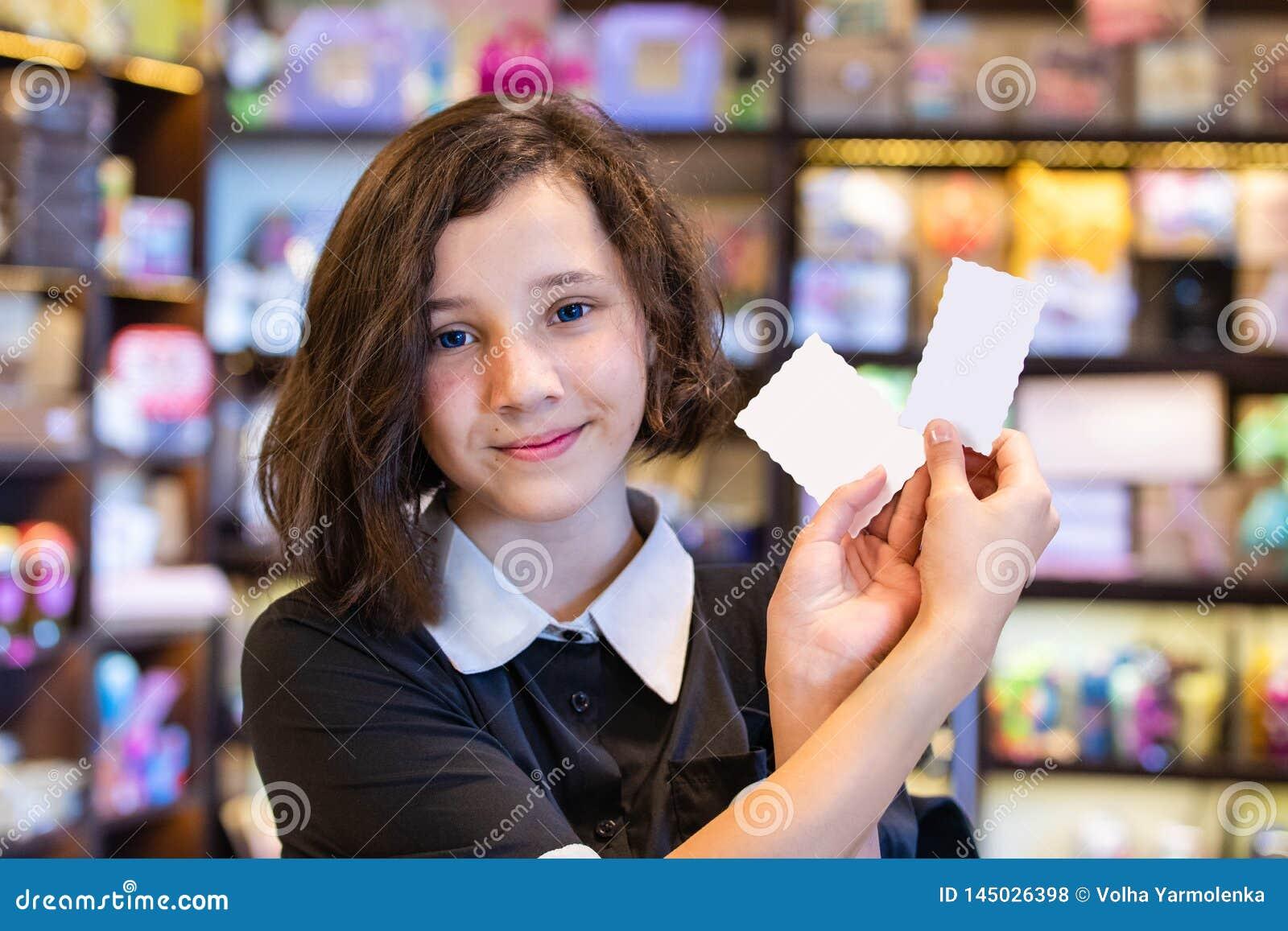 Menina bonito do jovem adolescente que guarda os cartões brancos no fundo da loja