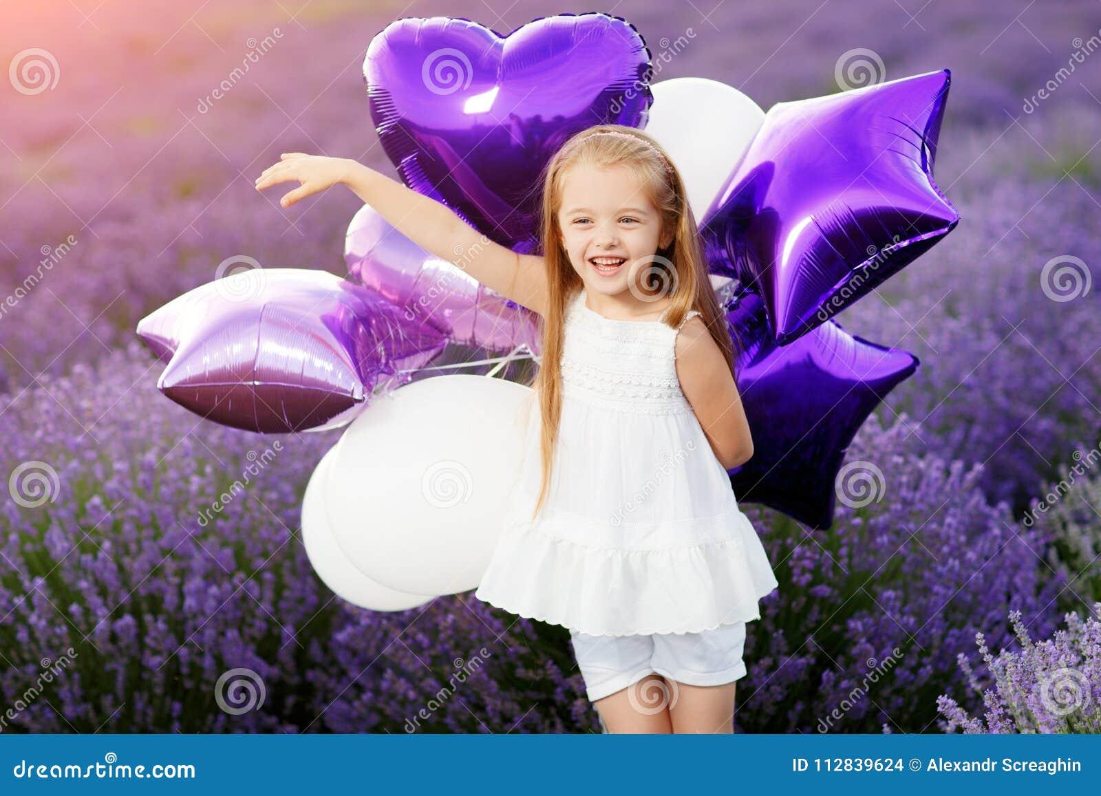 Menina bonito feliz no campo da alfazema com balões roxos Conceito da liberdade