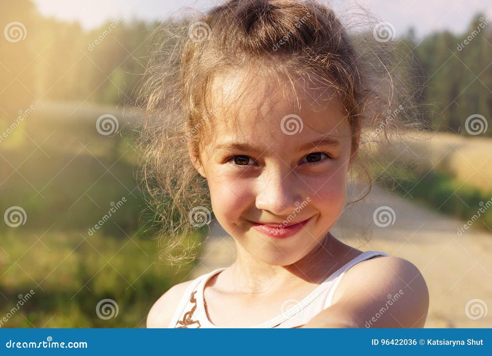 Menina bonito feliz que faz o selfie sobre o parque ensolarado Menina bonito do Preteen