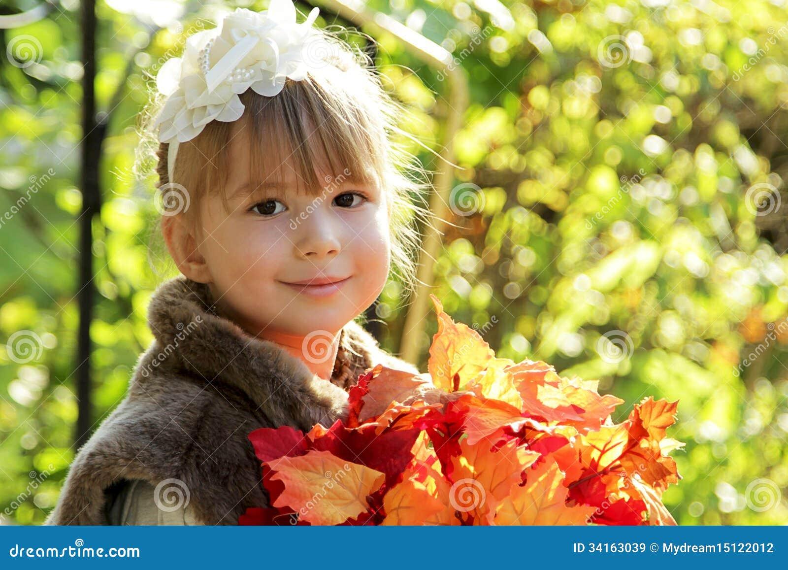 Menina bonito no parque do outono