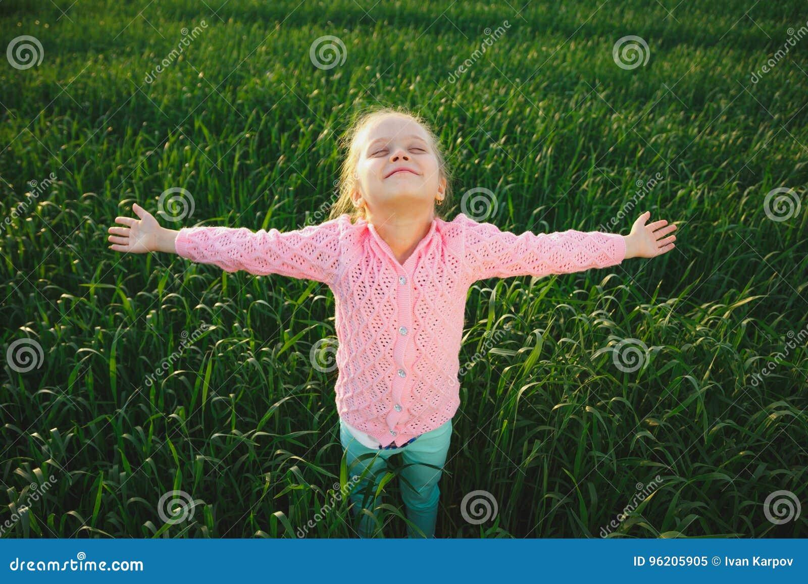 Menina bonito no prado no dia de verão