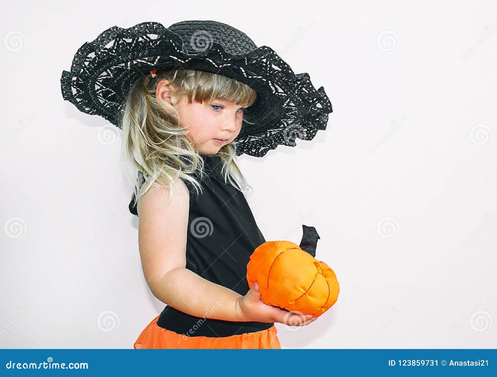 Menina bonito no traje da bruxa com abóboras Halloween Em um fundo branco