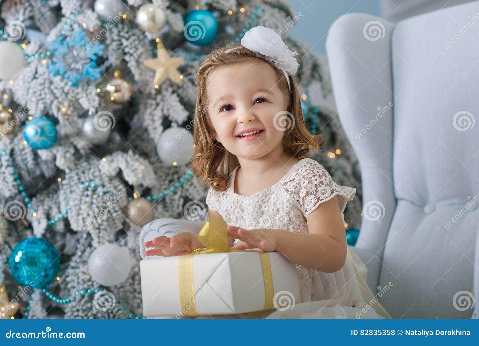 A menina bonito no vestido do bklom que senta-se em uma cadeira e abre a caixa com presente para o azul da árvore de Natal do fun