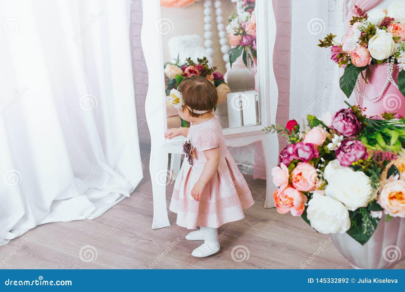 A menina bonito olha no espelho