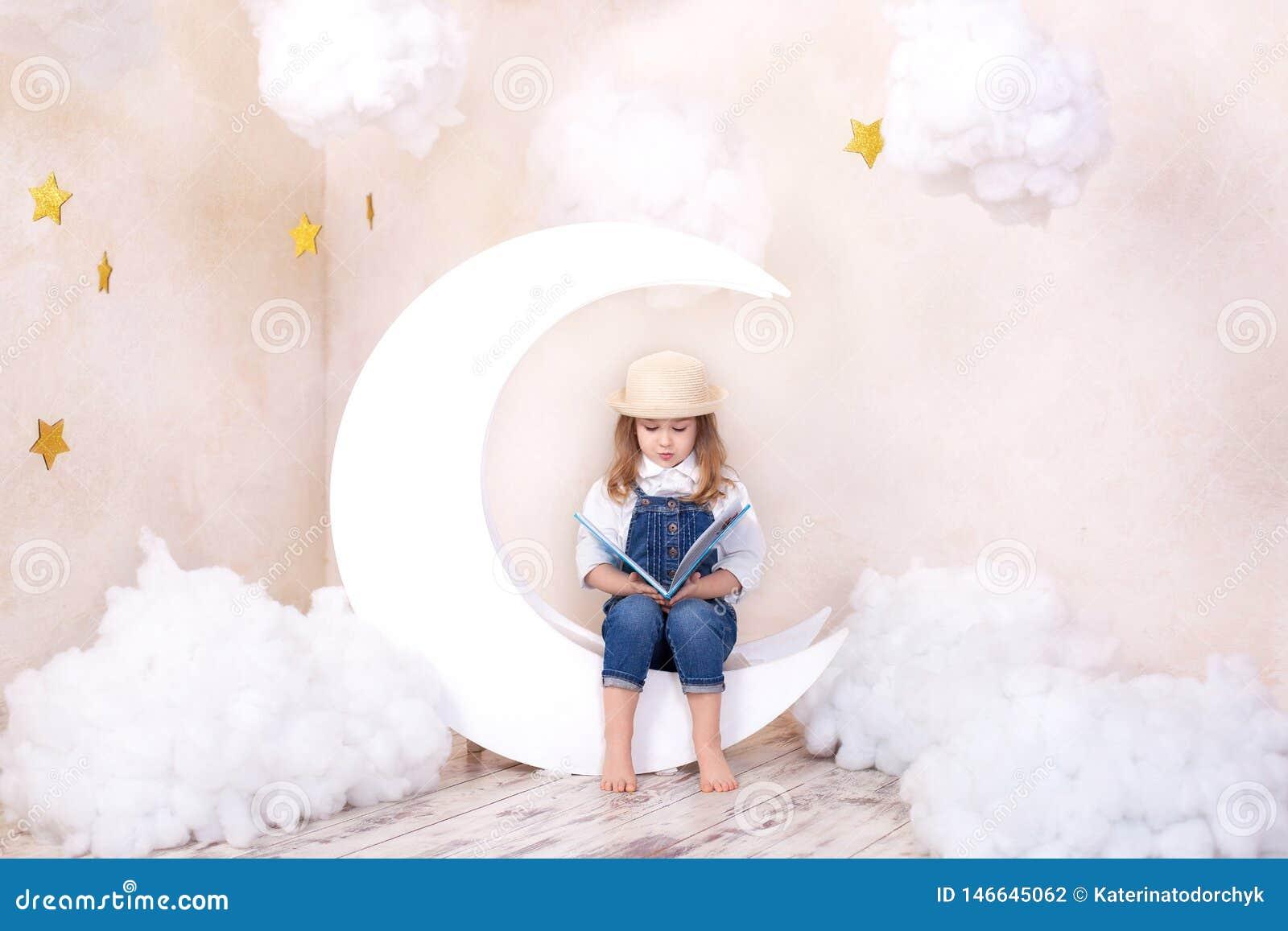 Menina bonito pequena que senta-se na lua com nuvens e estrelas com um livro em na suas mãos e leitura A menina est? aprendendo l