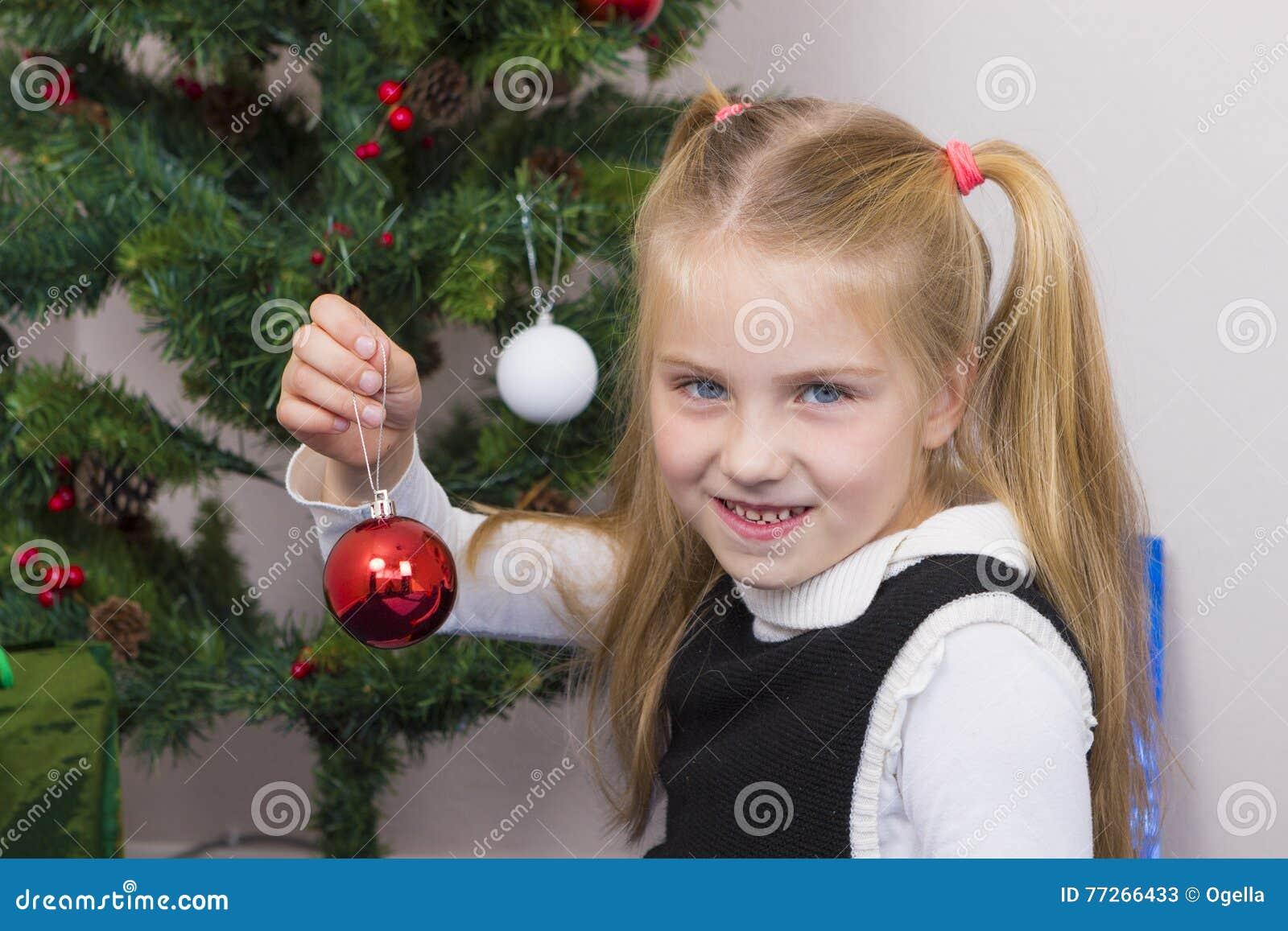 Menina bonito perto da árvore do ano novo