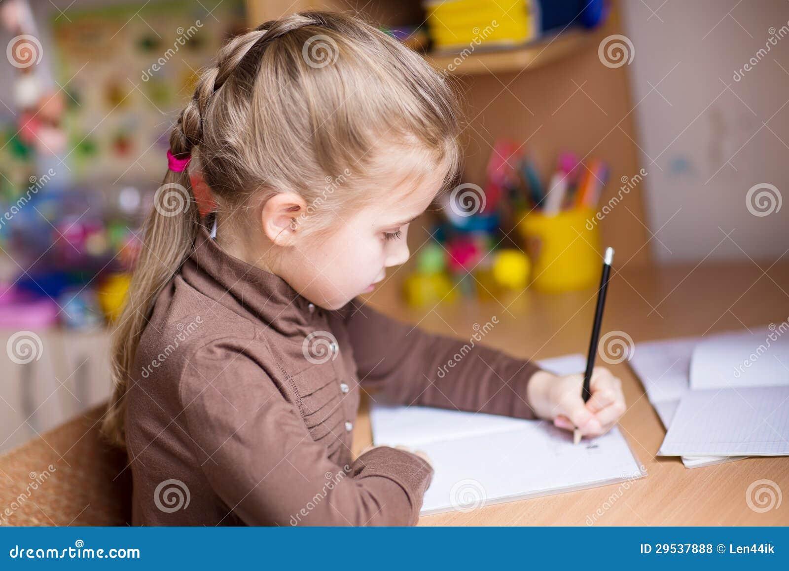 Menina bonito que escreve lhe trabalhos de casa