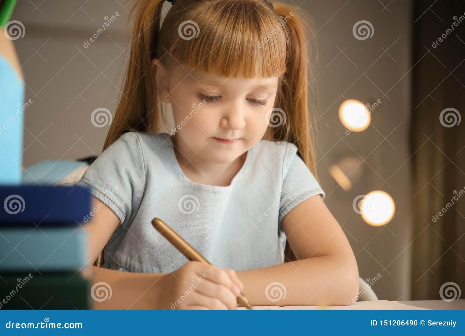 Menina bonito que faz suas lições em casa