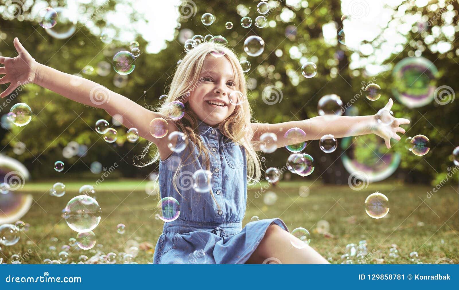 Menina bonito que joga bolhas de sabão