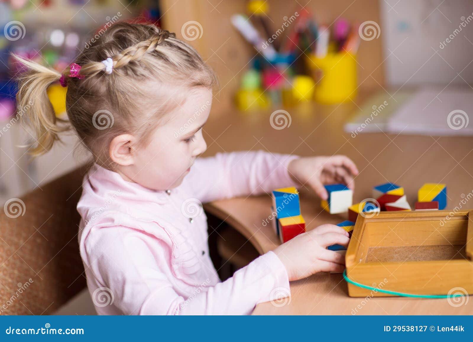 Menina bonito que joga com blocos