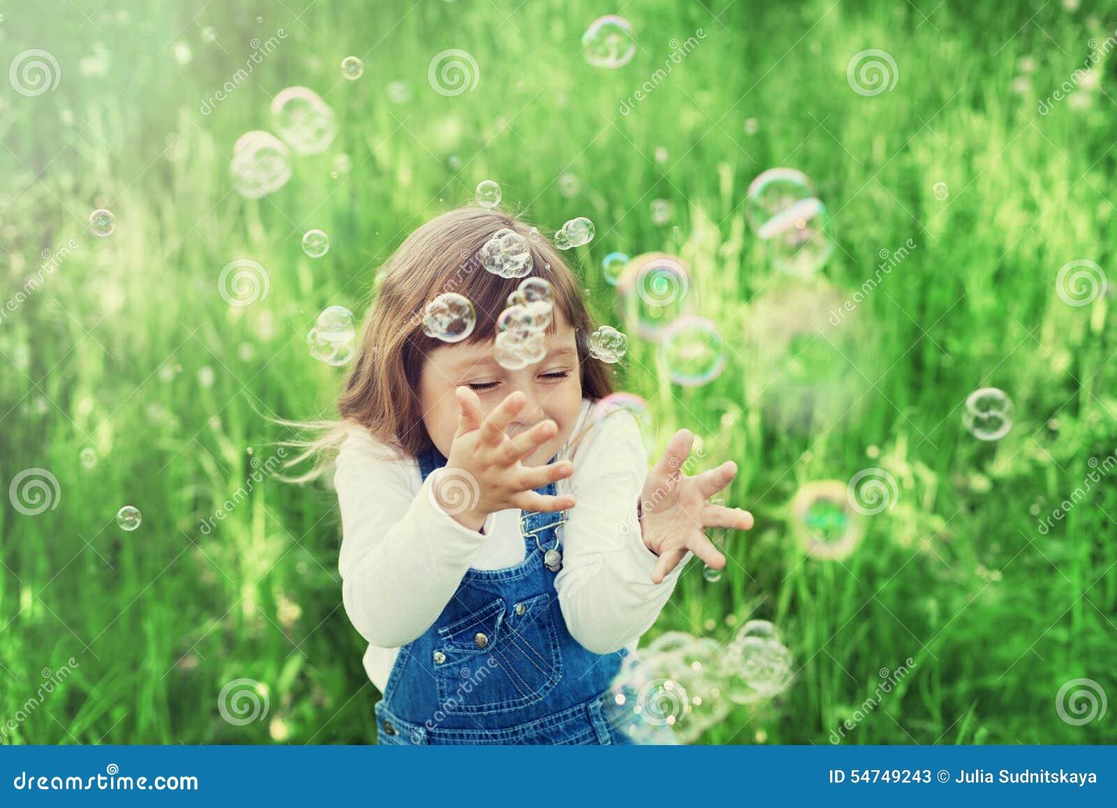 Menina bonito que joga com bolhas de sabão no gramado verde exterior, conceito feliz da infância, criança que tem o divertimento