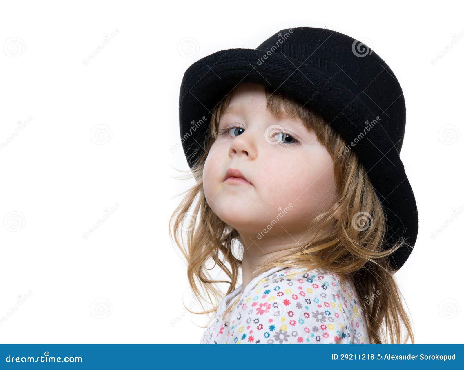 Menina bonito que levanta no chapéu negro