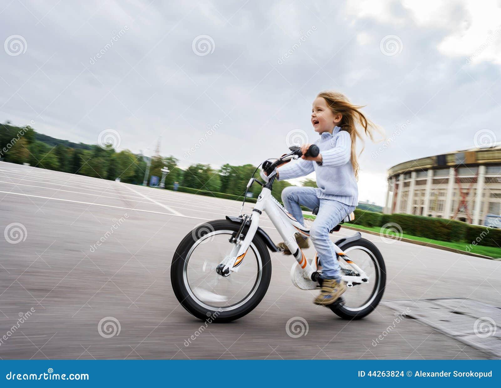 Menina bonito que monta rapidamente pela bicicleta