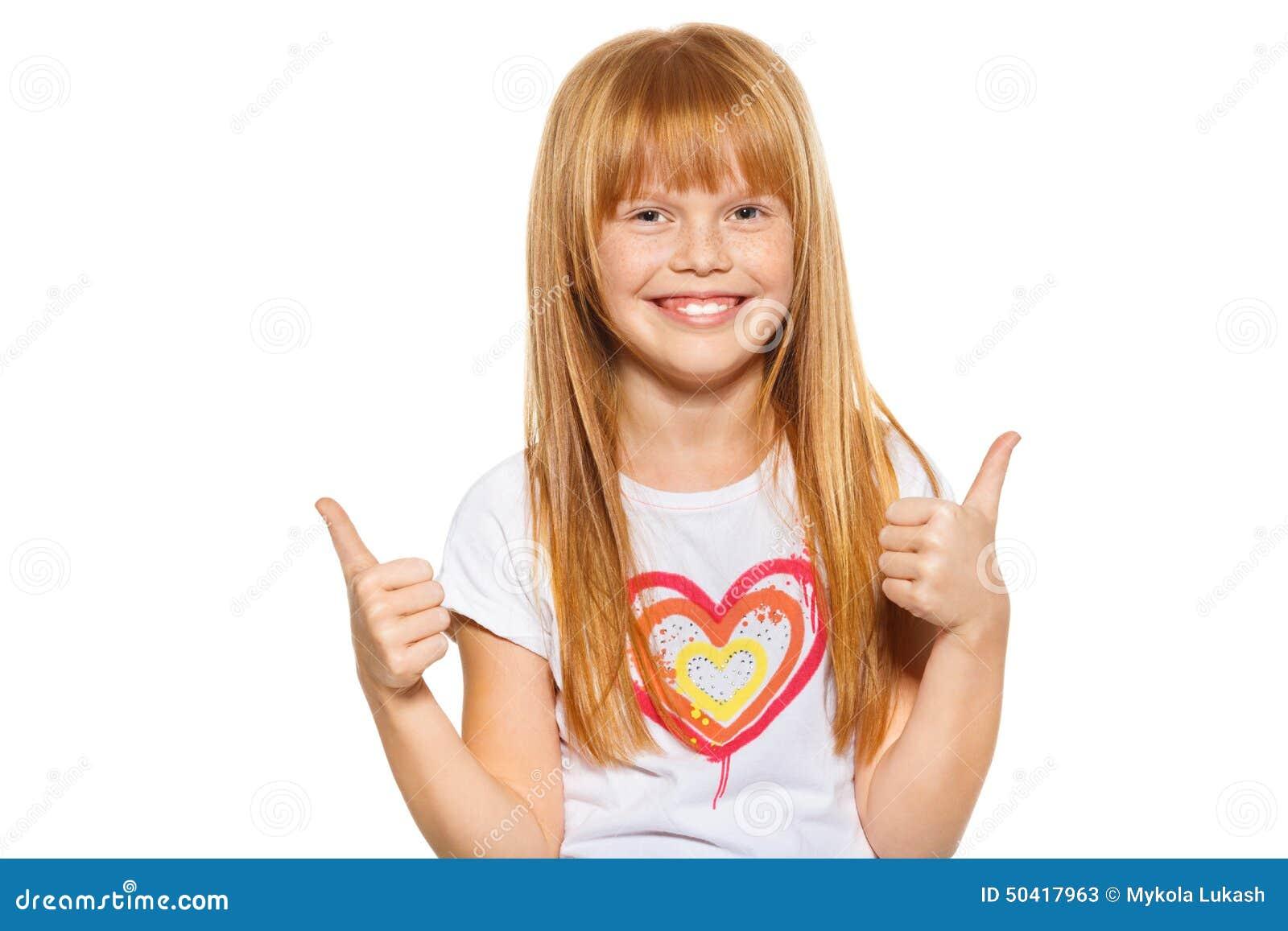 Menina bonito que mostra os polegares acima com ambas as mãos, isoladas no branco