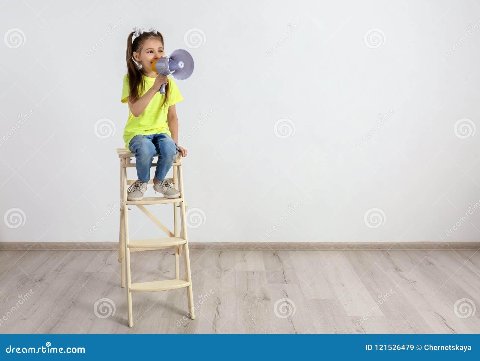 Menina bonito que senta-se com megafone