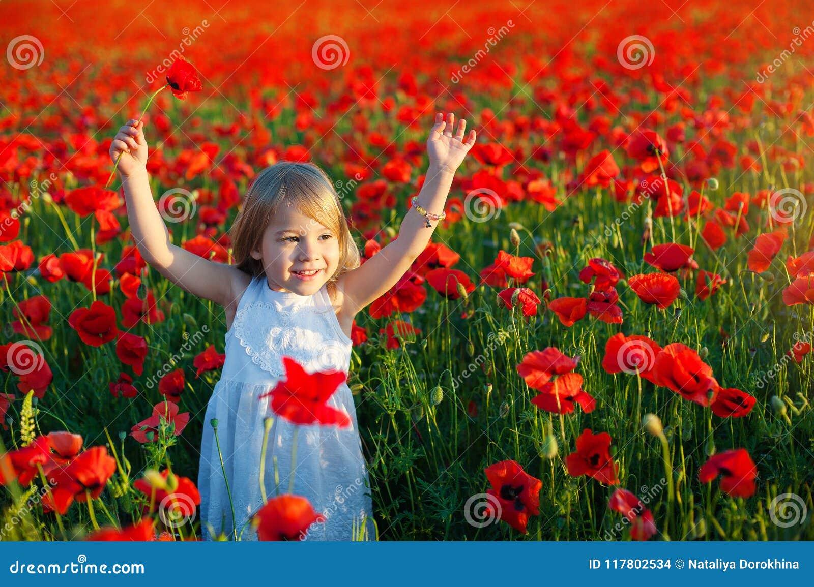 A menina bonito sorri e aumenta seus braços para cima para a alegria campos da papoila em Itália