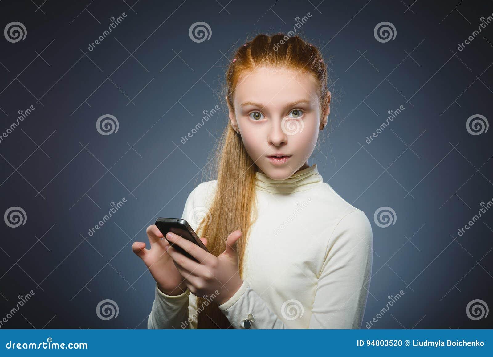 Menina bonito surpreendida do ruivo com telefone celular Isolado no cinza