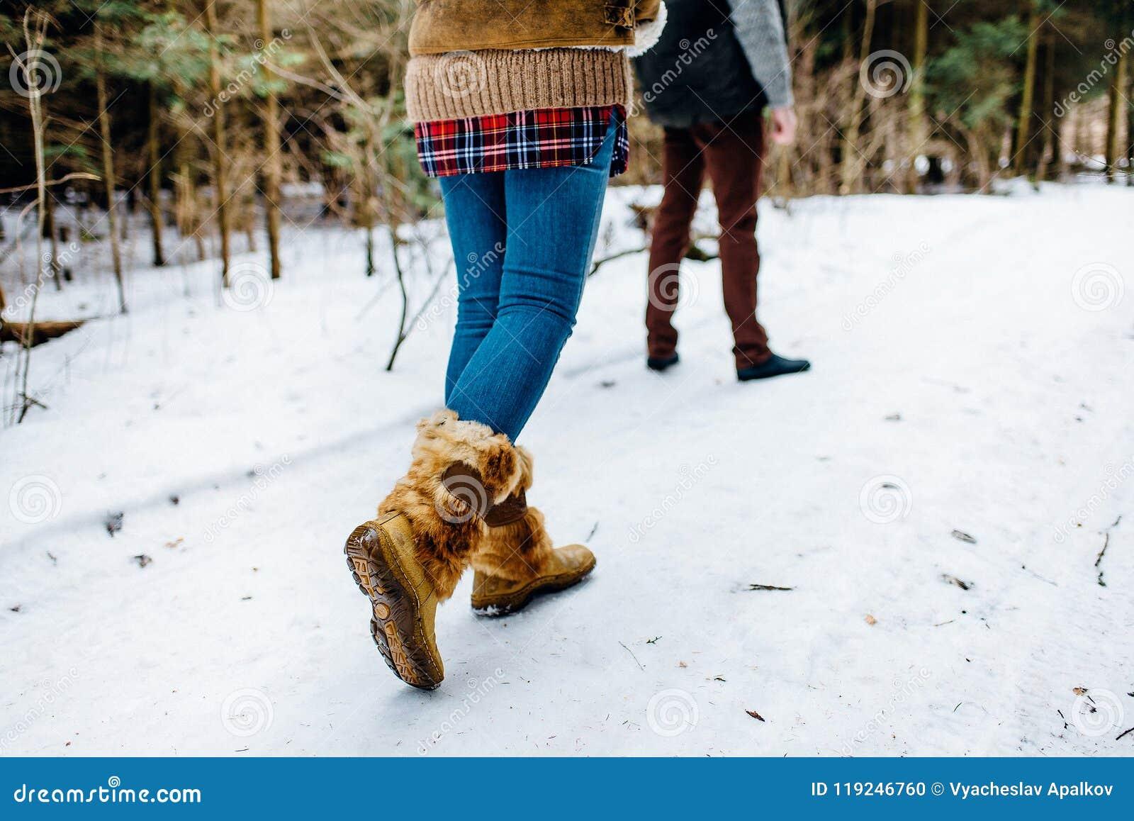Menina calorosamente vestida que alcança um homem ereto com madeira do inverno