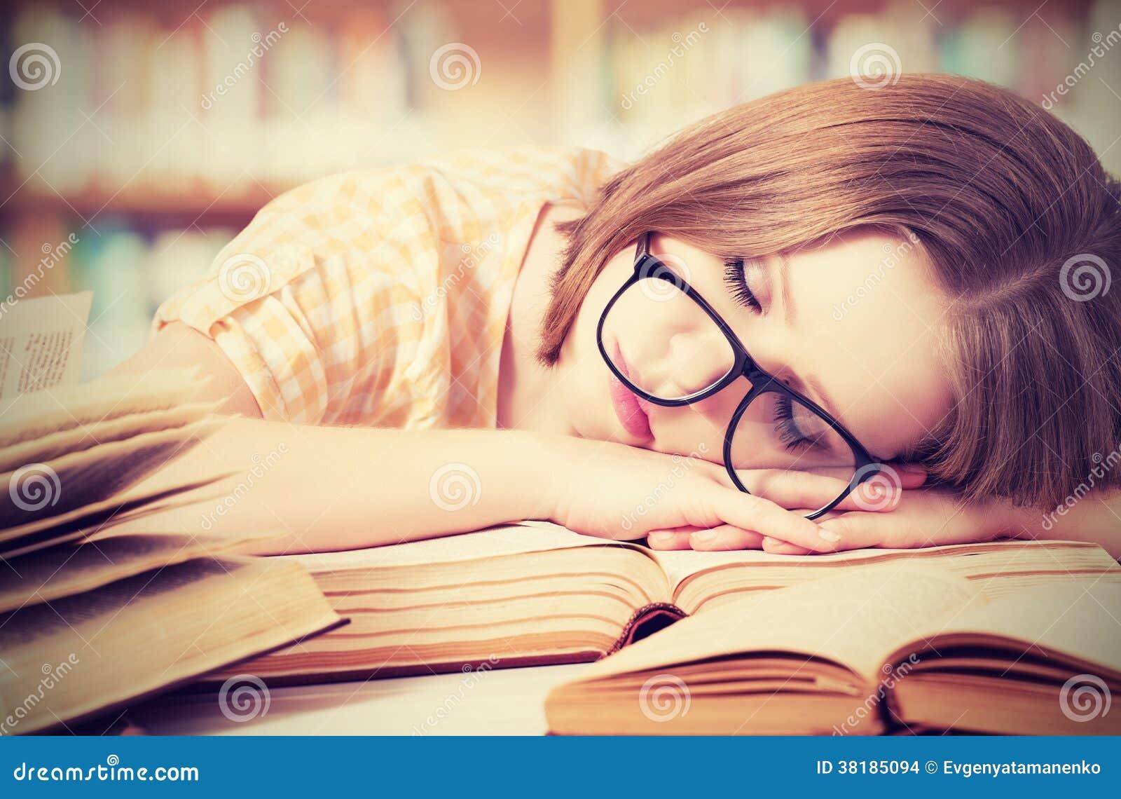 Menina cansado do estudante com vidros que dorme em livros na biblioteca