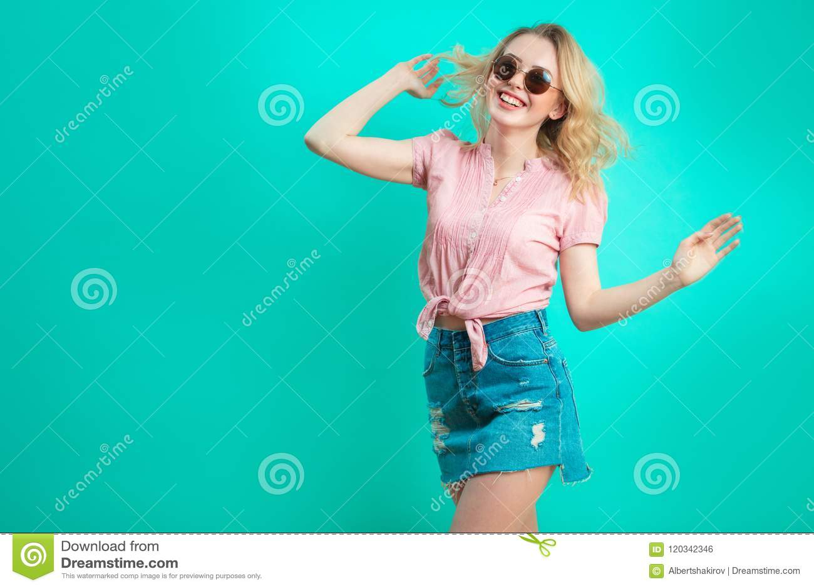 Menina caucasiano alegre com o cabelo encaracolado longo isolado no fundo azul