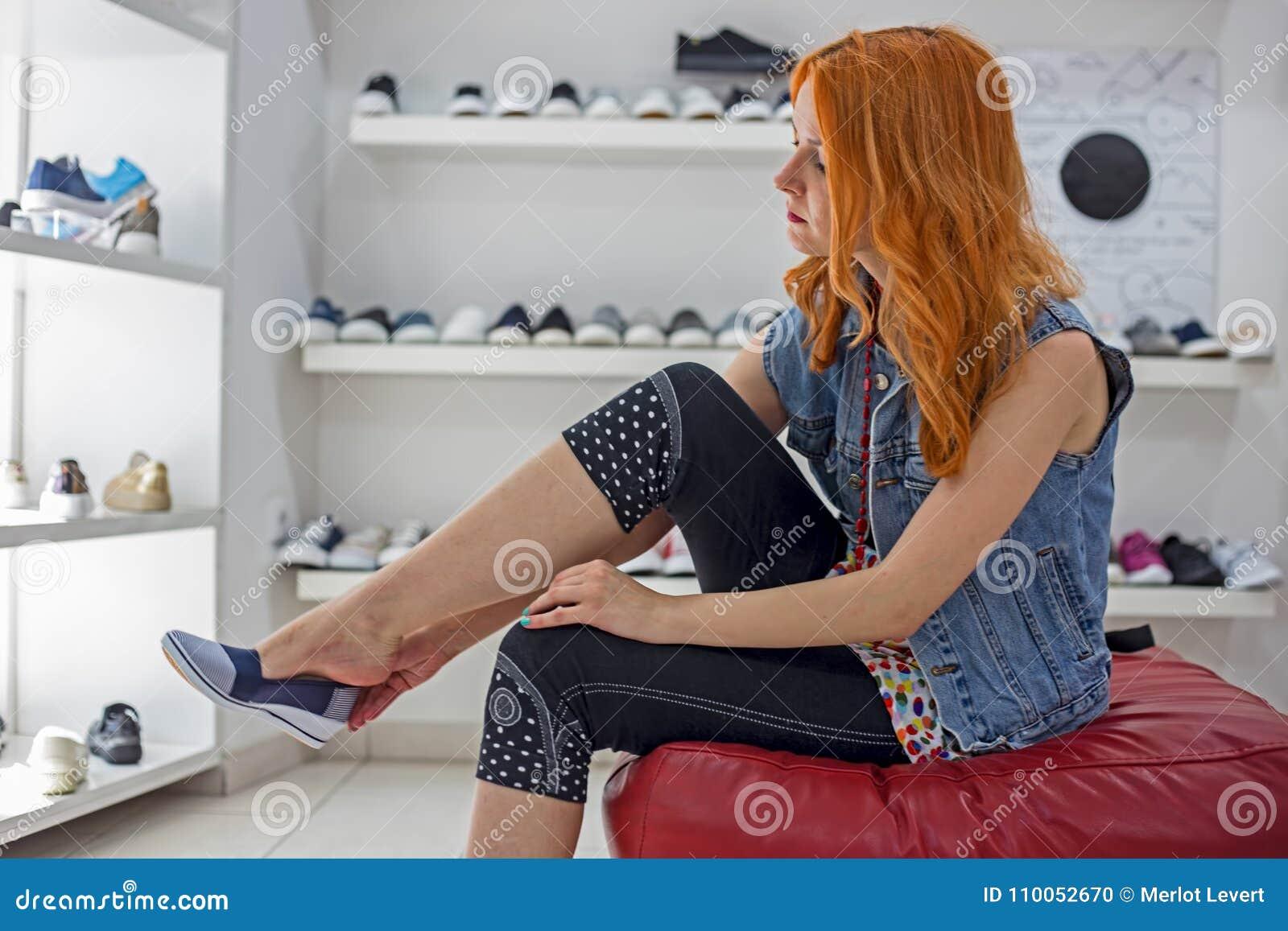 Menina caucasiano do ruivo bonito que escolhe e que veste sapatas novas na loja