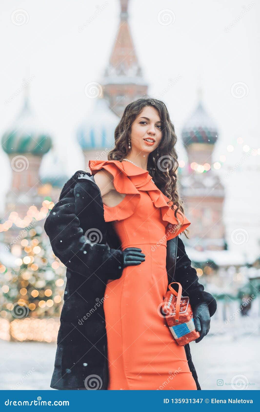 A menina caucasiano em um vestido vermelho guarda à disposição um acordeão no fundo do inverno da catedral da manjericão do St