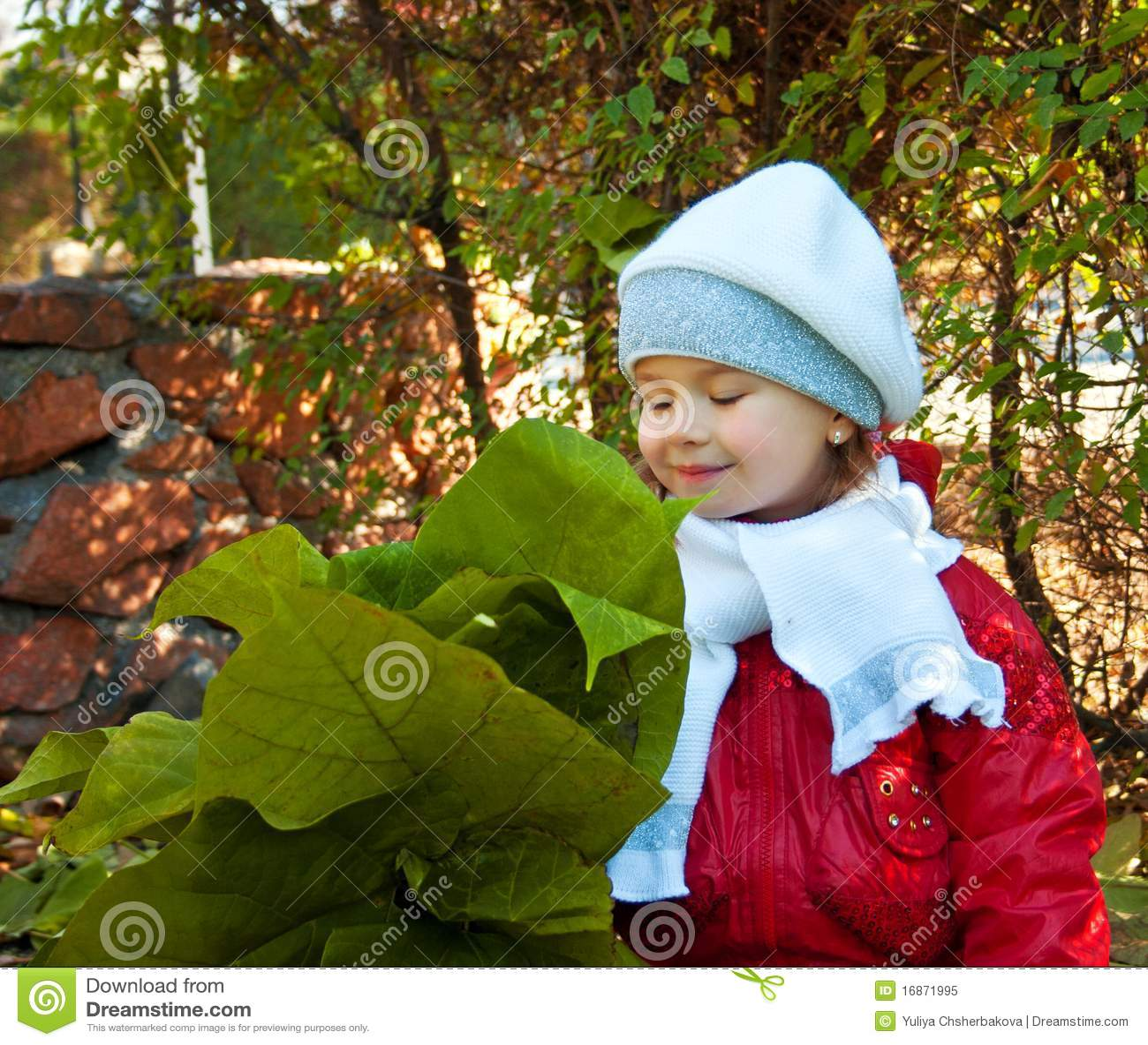 A menina cheira as folhas