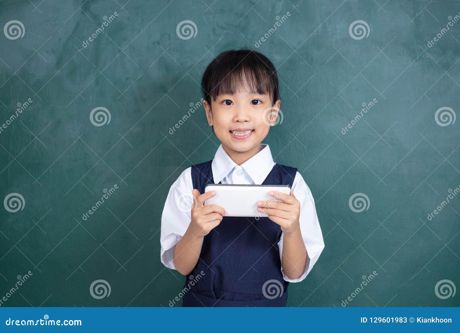 Menina chinesa asiática no uniforme que joga o agai digital da tabuleta