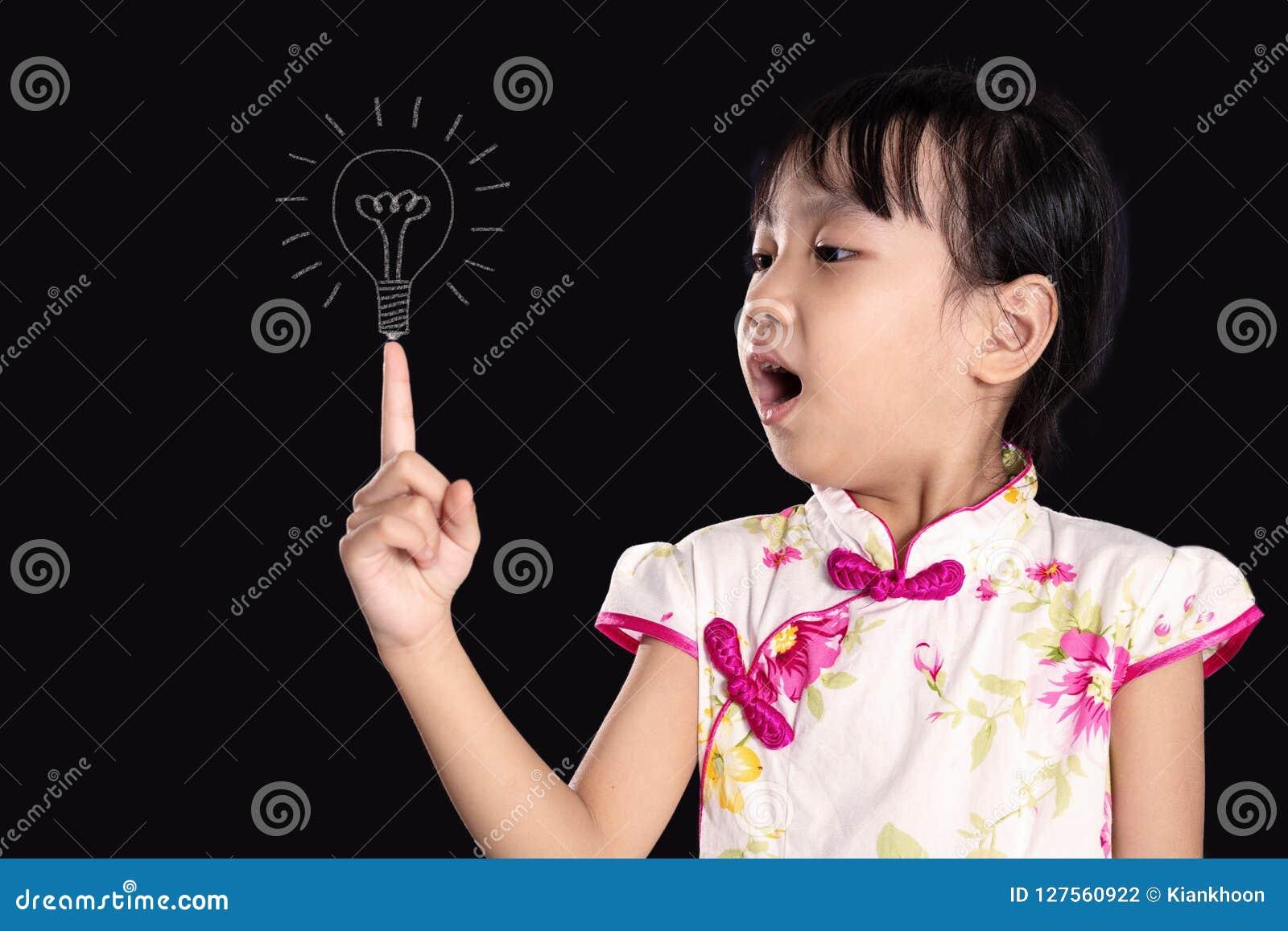 Menina chinesa asiática que aponta o dedo até o bulbo