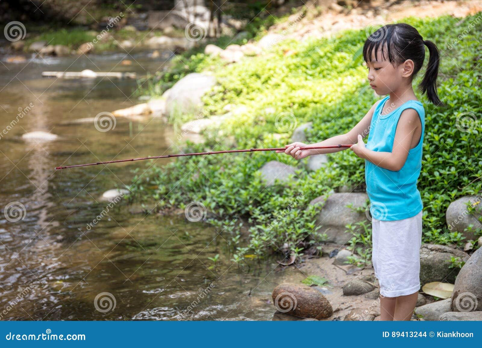 Menina chinesa asiática que dobra com vara de pesca