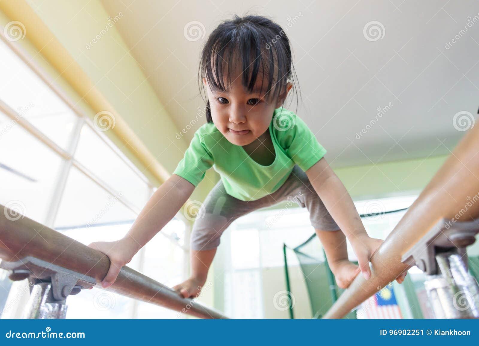 Menina chinesa asiática que escala em barras paralelas