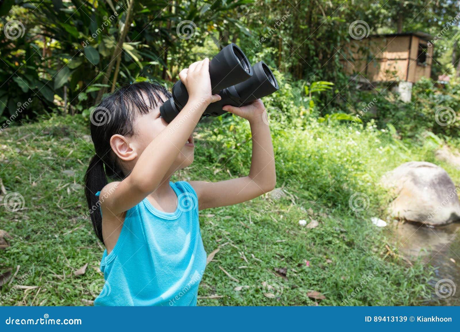 Menina chinesa asiática que explora ao redor com binóculos