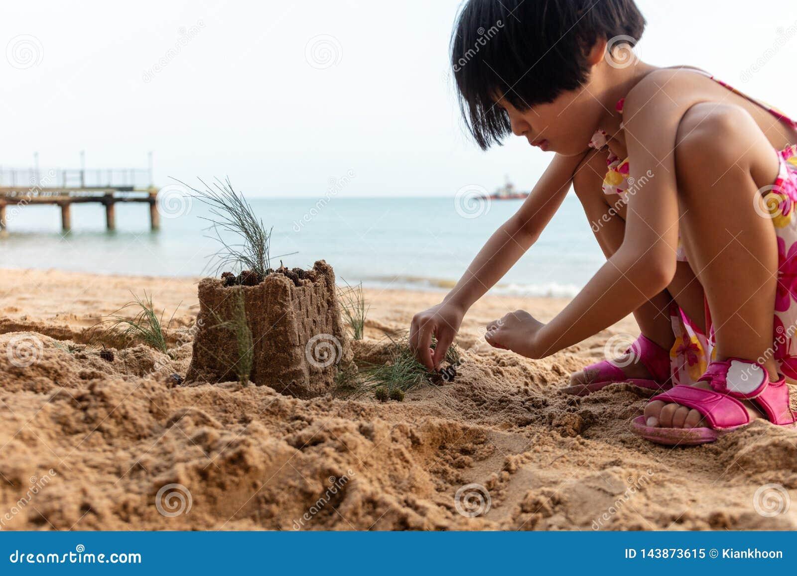 Menina chinesa asiática que joga a areia na praia