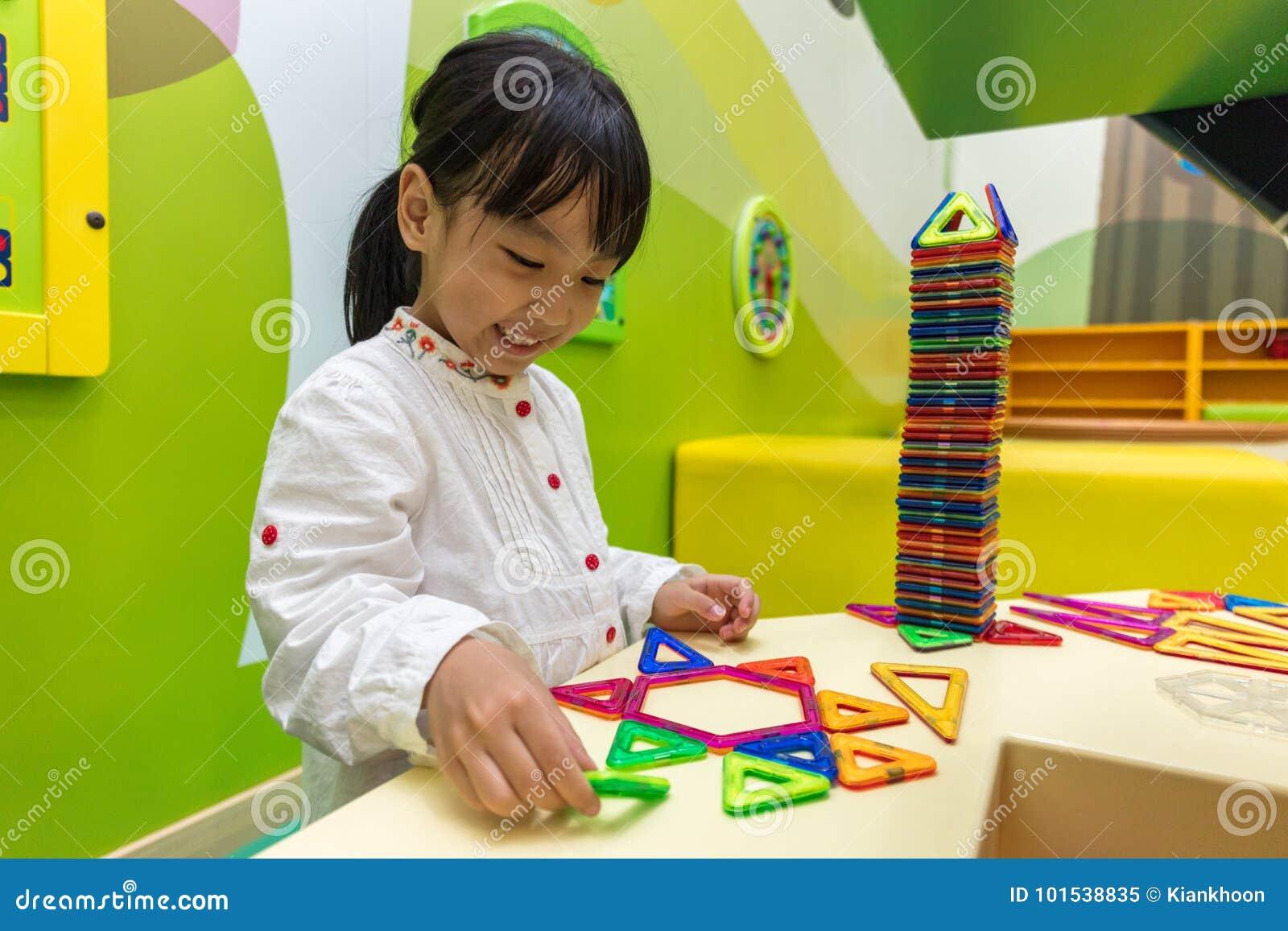 Menina chinesa asiática que joga blocos coloridos do plástico do ímã