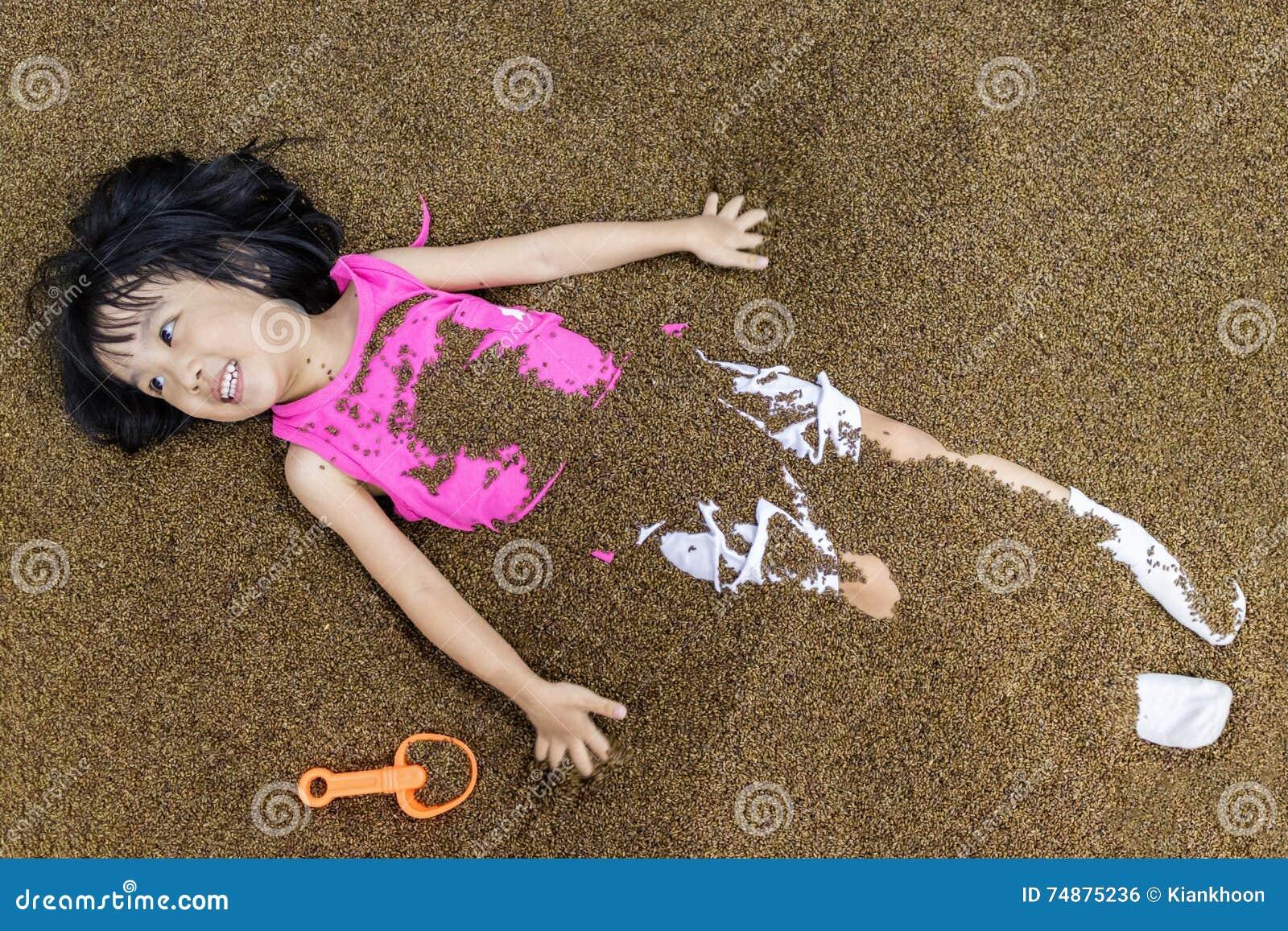 Menina chinesa asiática que joga com areia