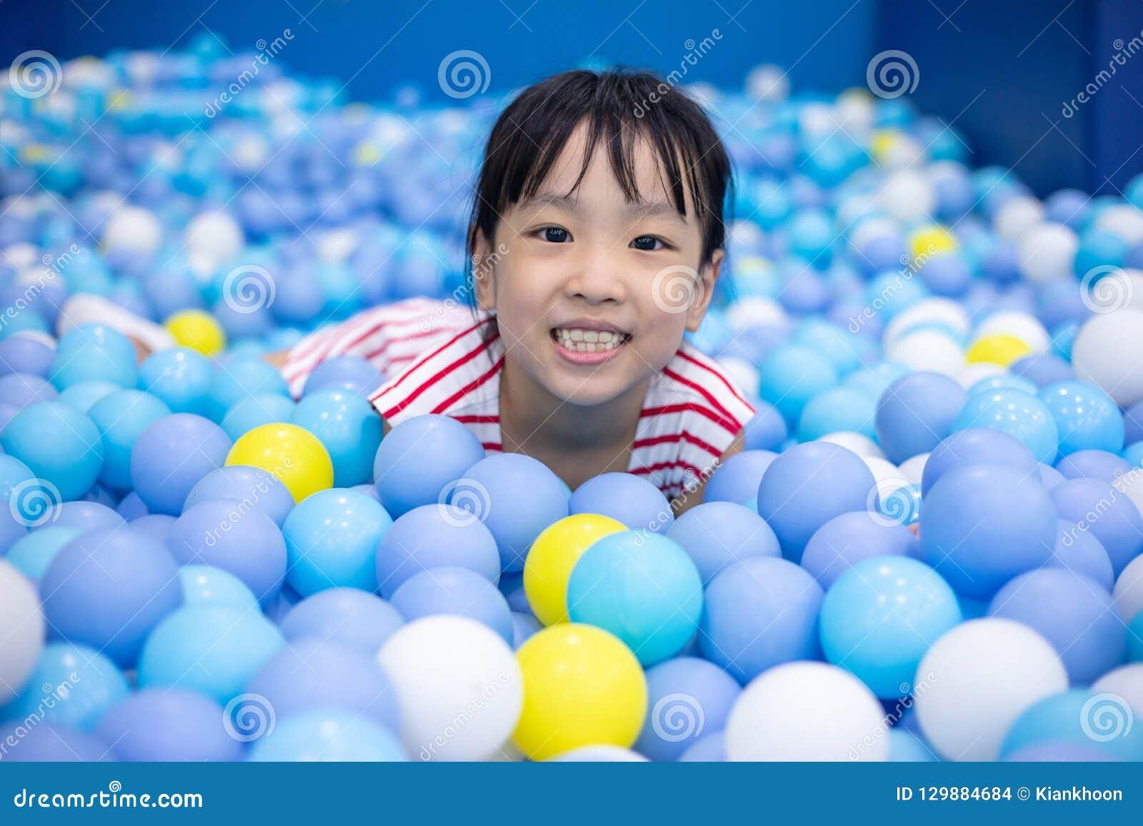 Menina chinesa asiática que joga na associação das bolas
