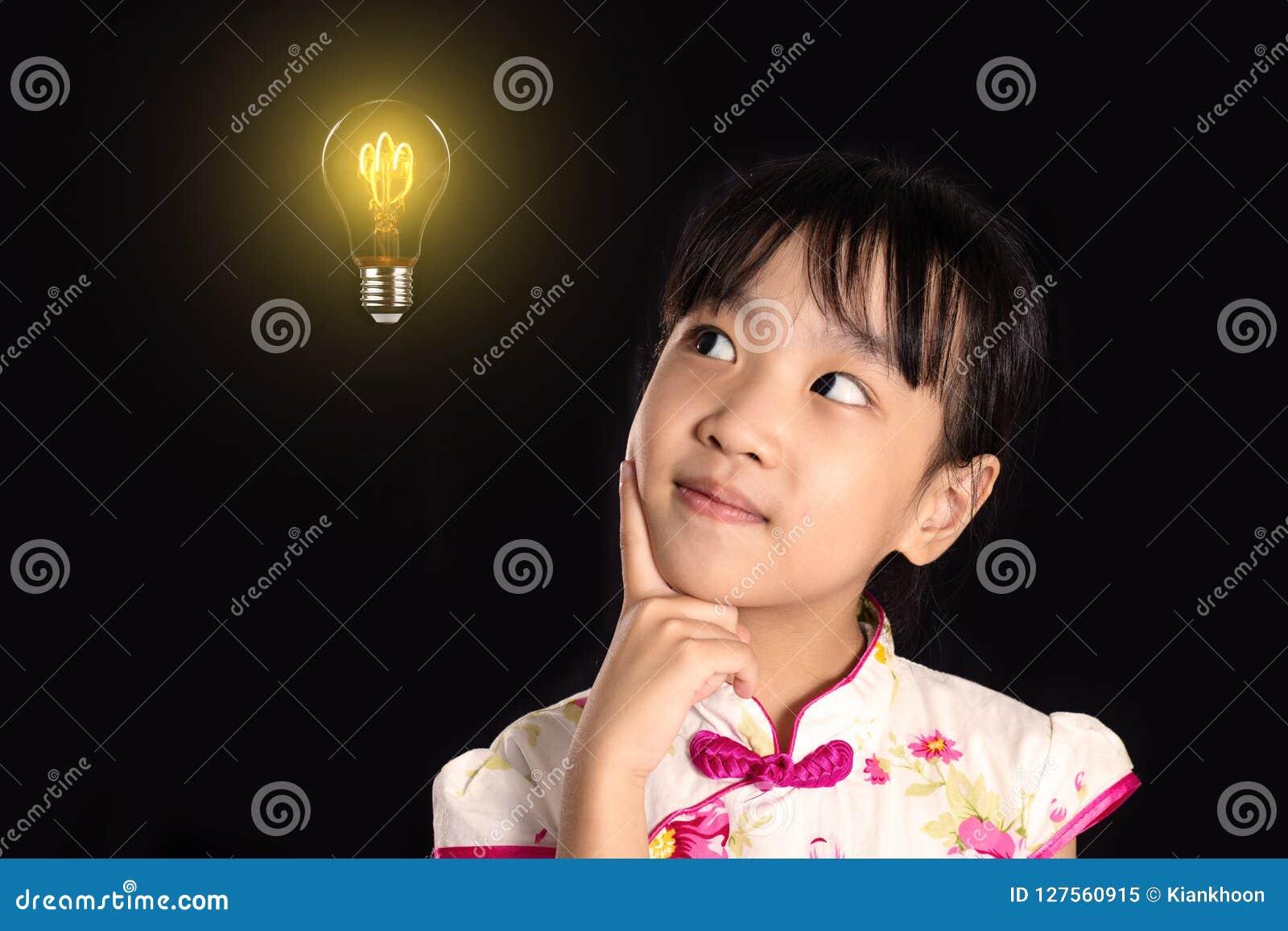 Menina chinesa asiática que pensa com ampola