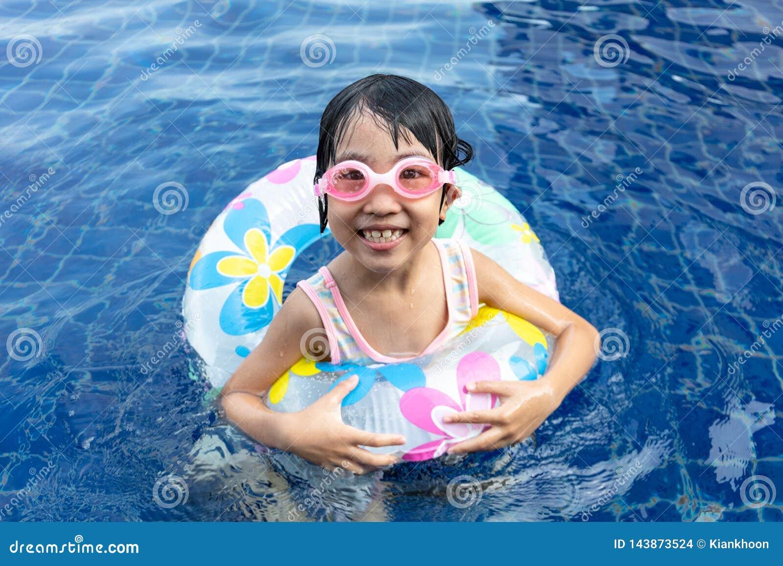Menina chinesa pequena asiática que joga na piscina