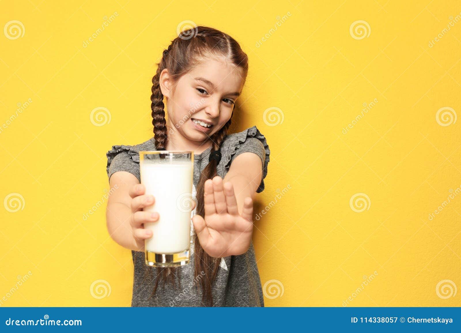 Menina com a alergia da leiteria que guarda o vidro do leite