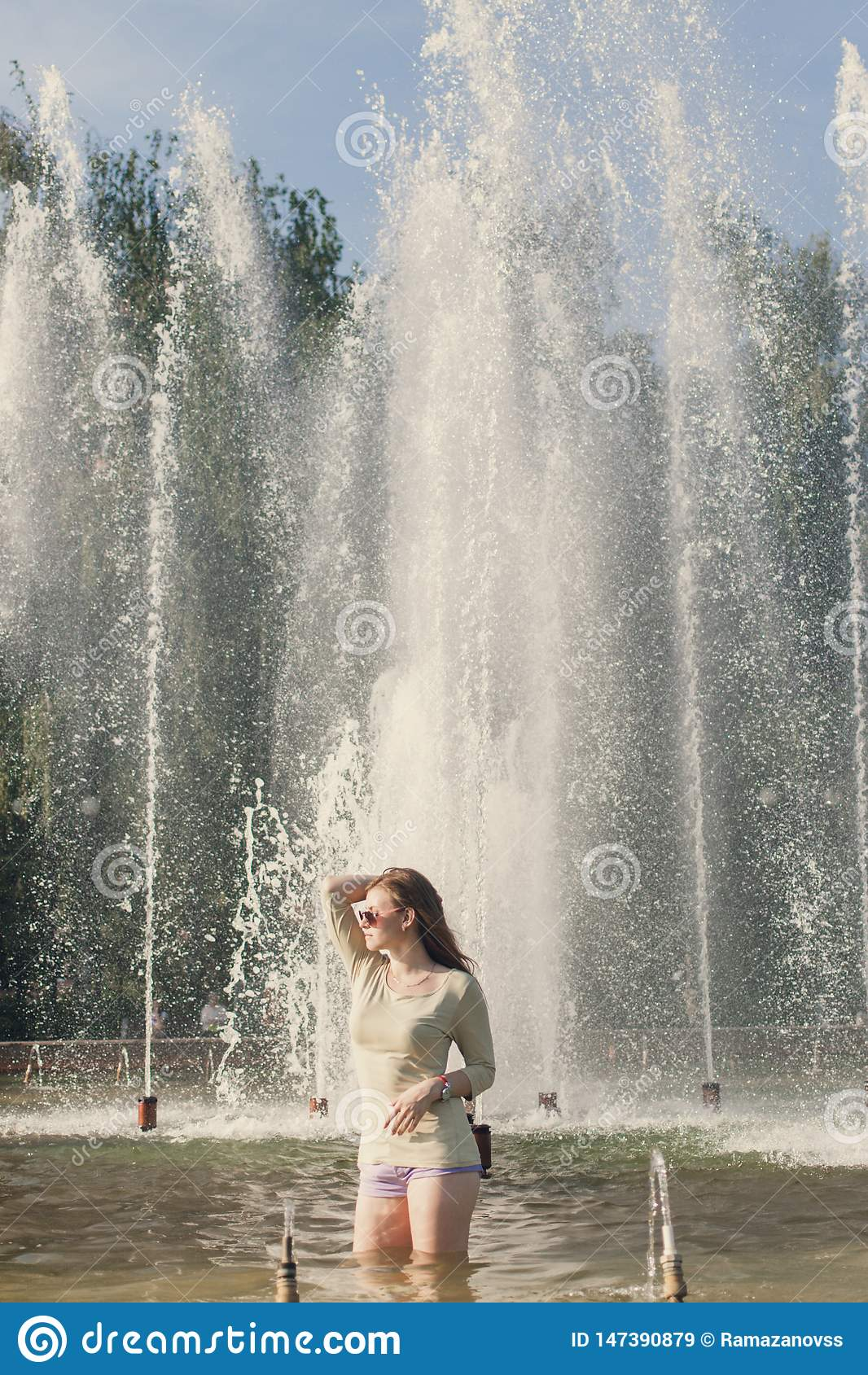 A menina com cabelo de fluxo no short curto e nos ?culos de sol est? estando na fonte