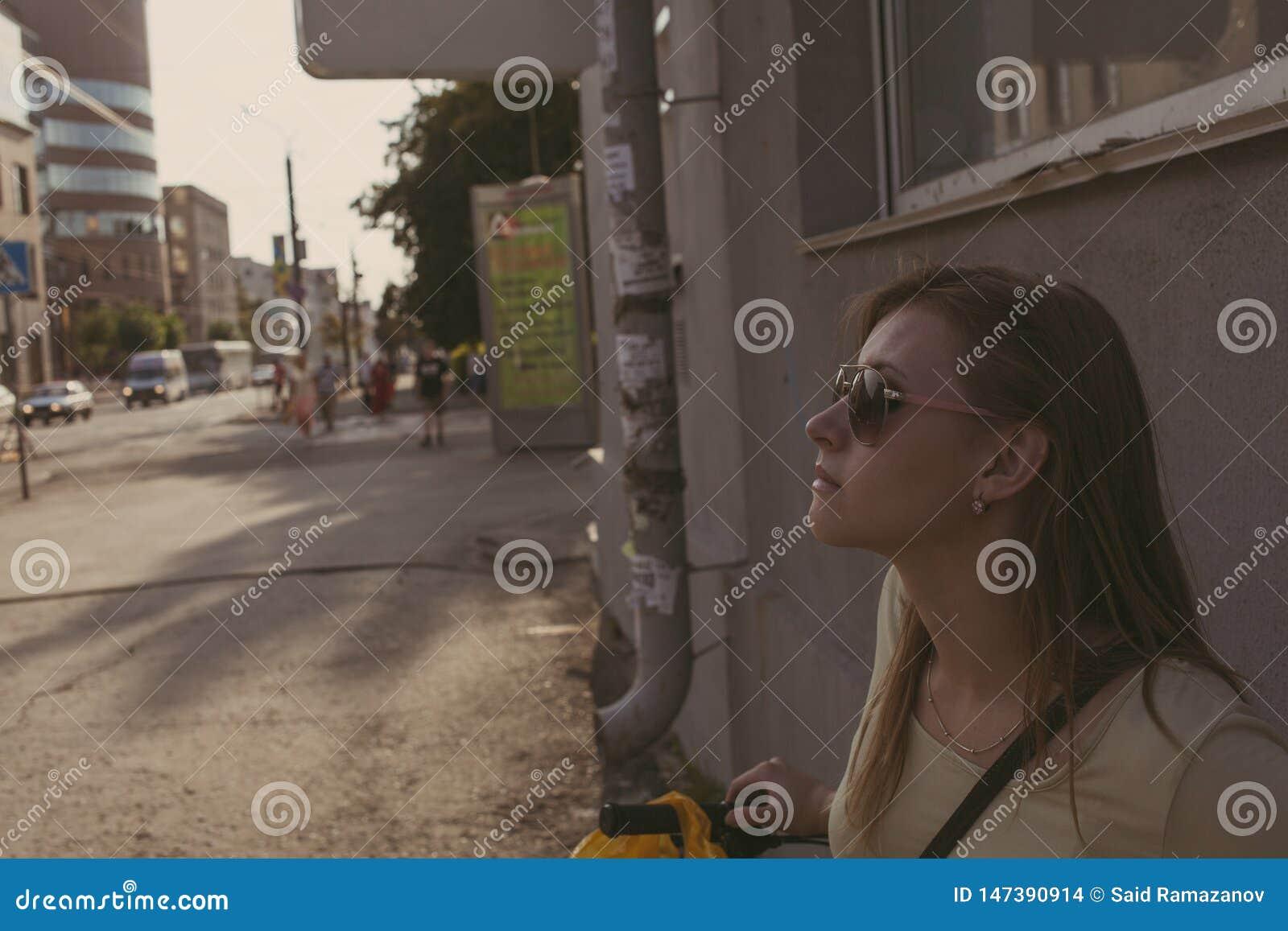 A menina com cabelo de fluxo nos óculos de sol está contra uma parede na cidade
