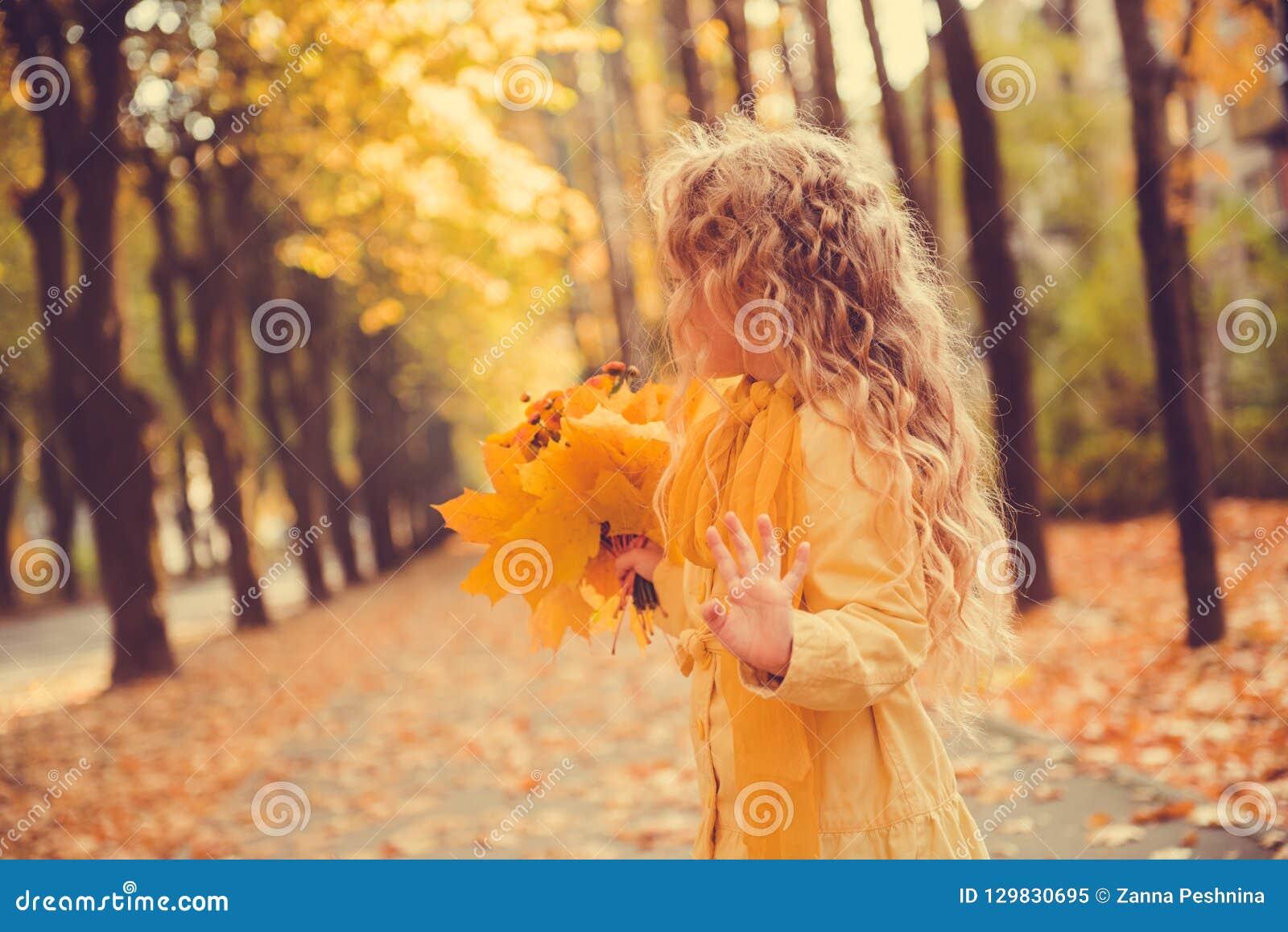 Menina com cabelo louro no fundo do outono