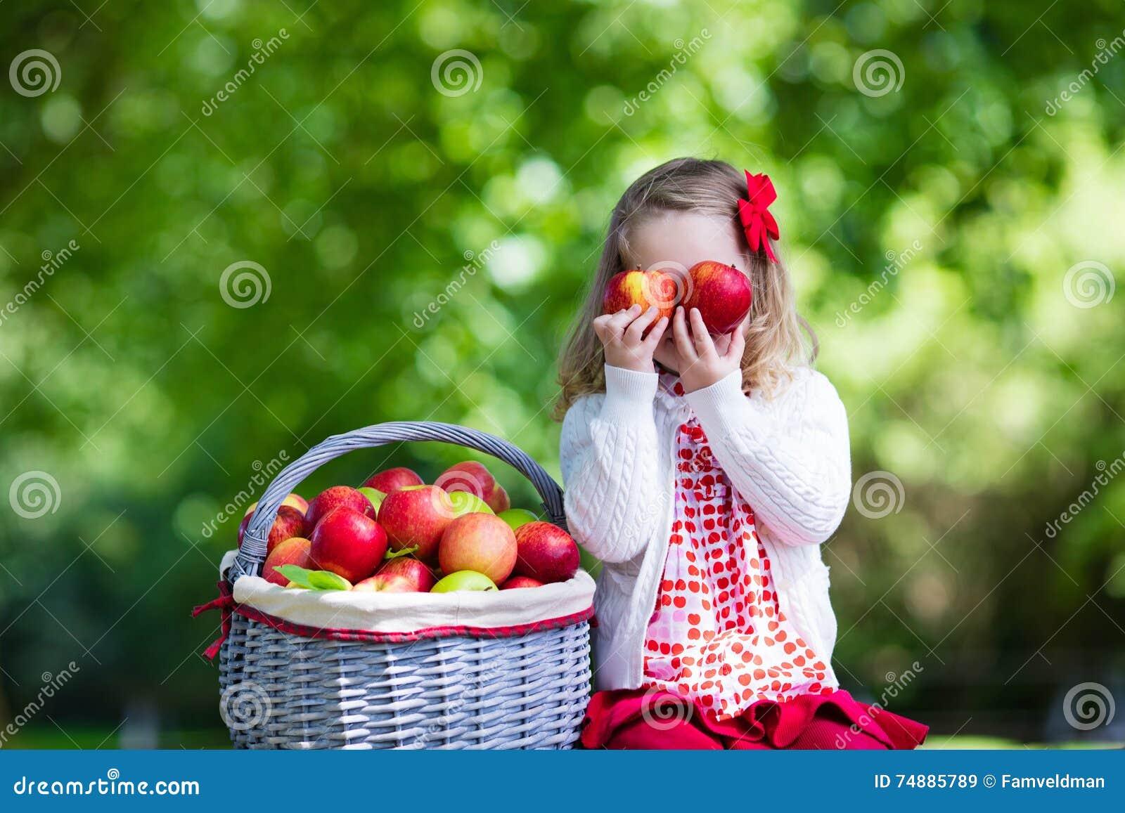 Menina com cesta da maçã