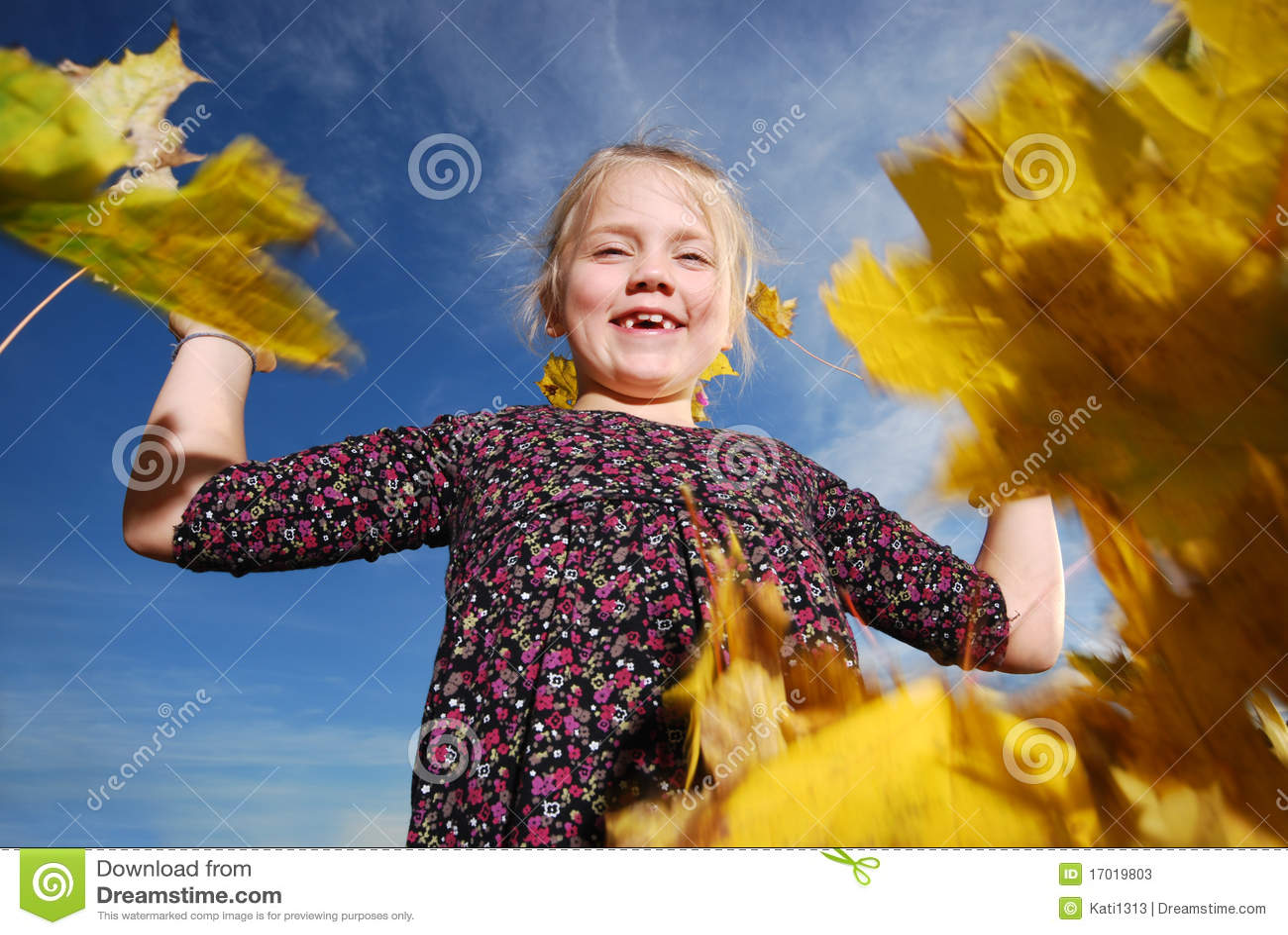 Menina com folhas do outono