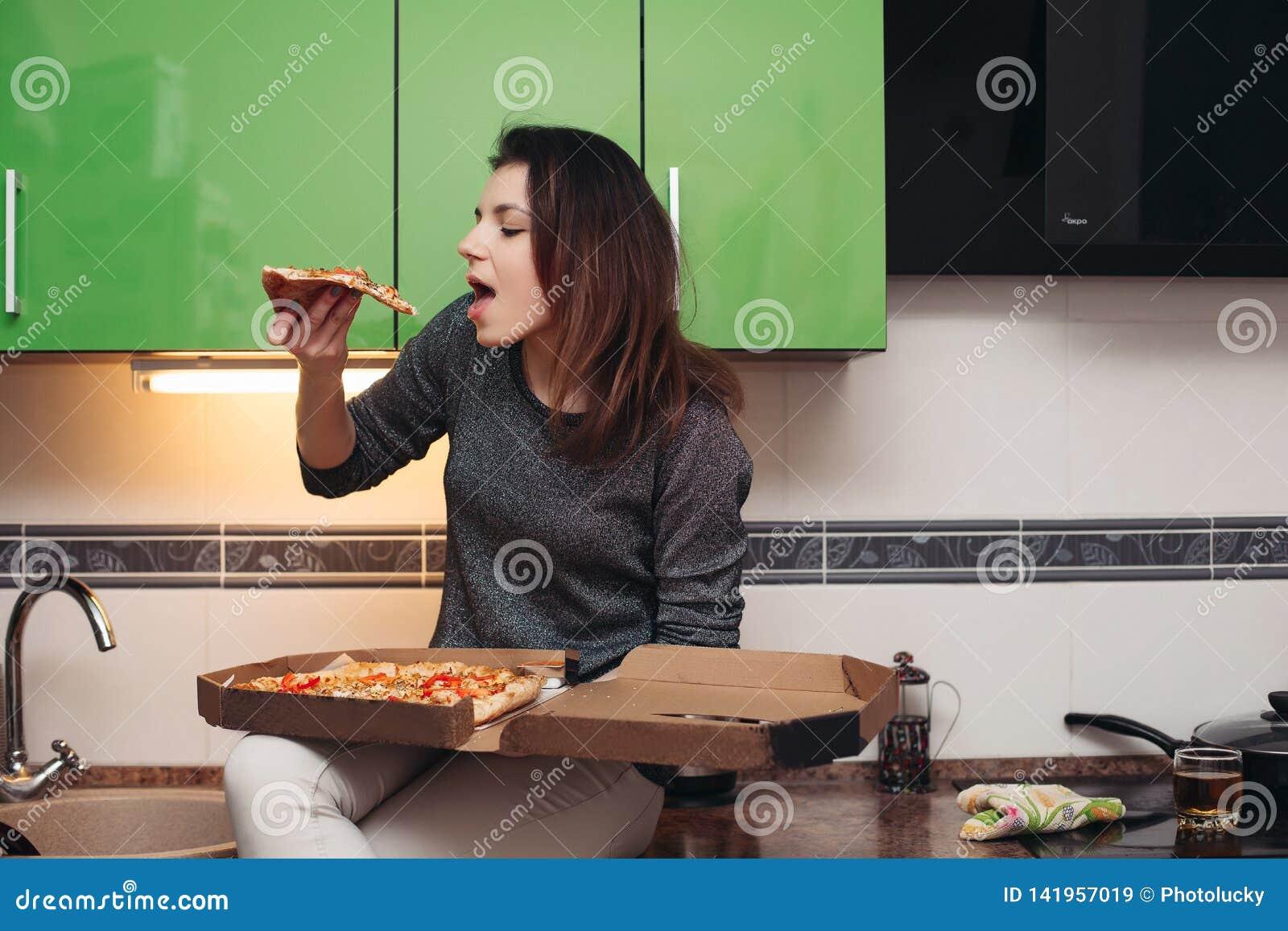 Menina com fome que senta-se na cozinha e que come a pizza saboroso