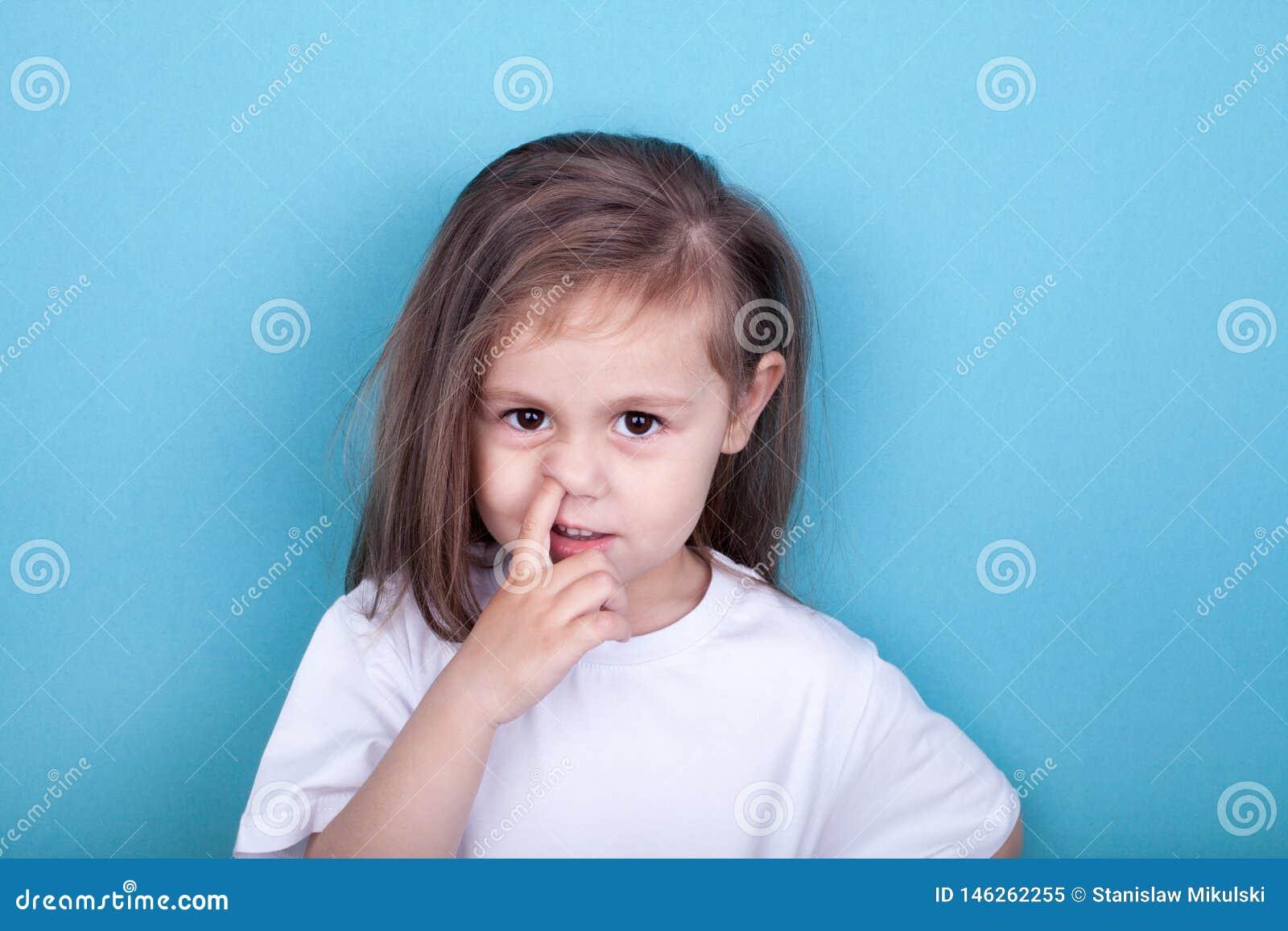 Menina com o dedo em seu nariz