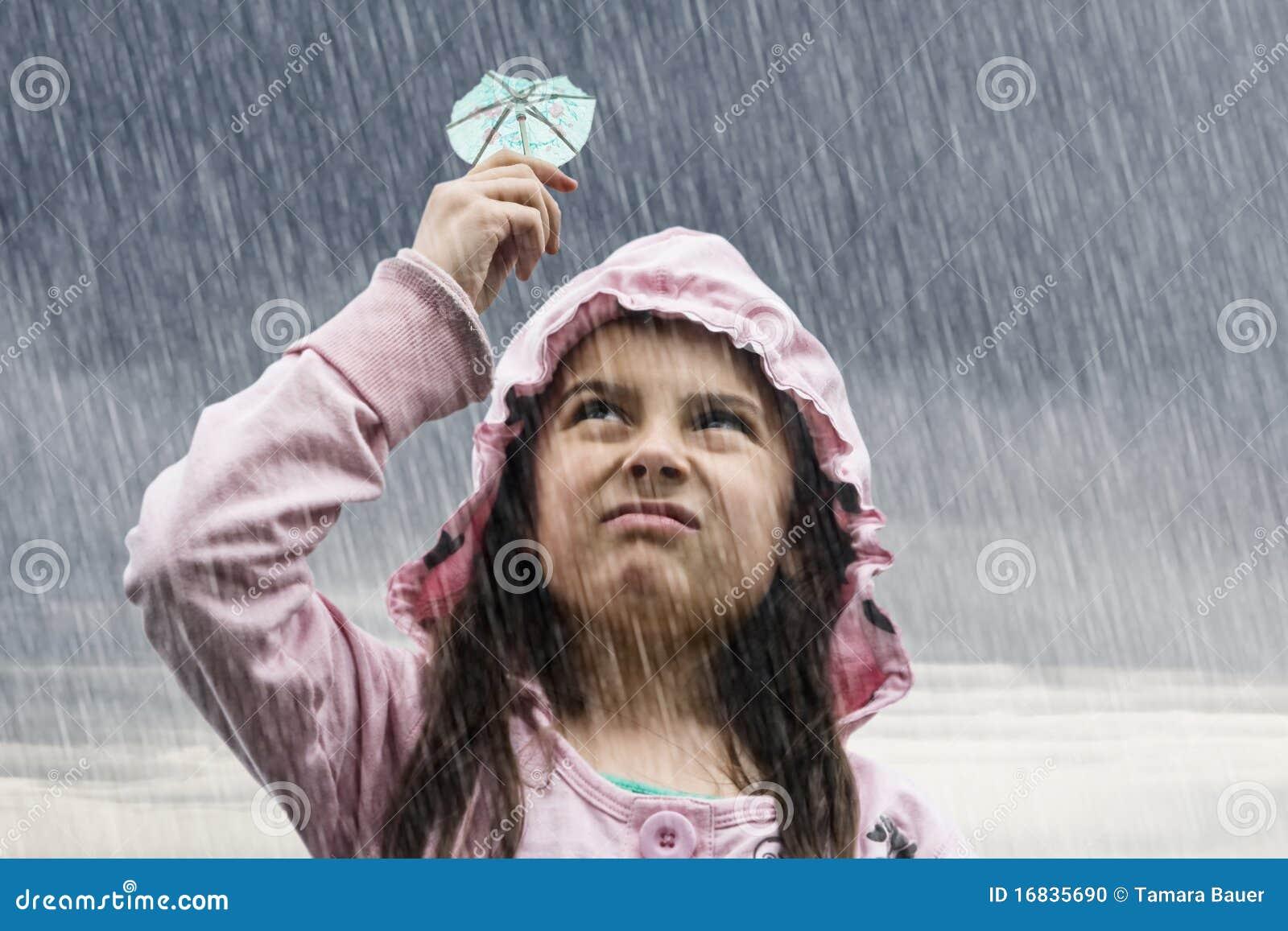 Menina com o guarda-chuva do cocktail na chuva