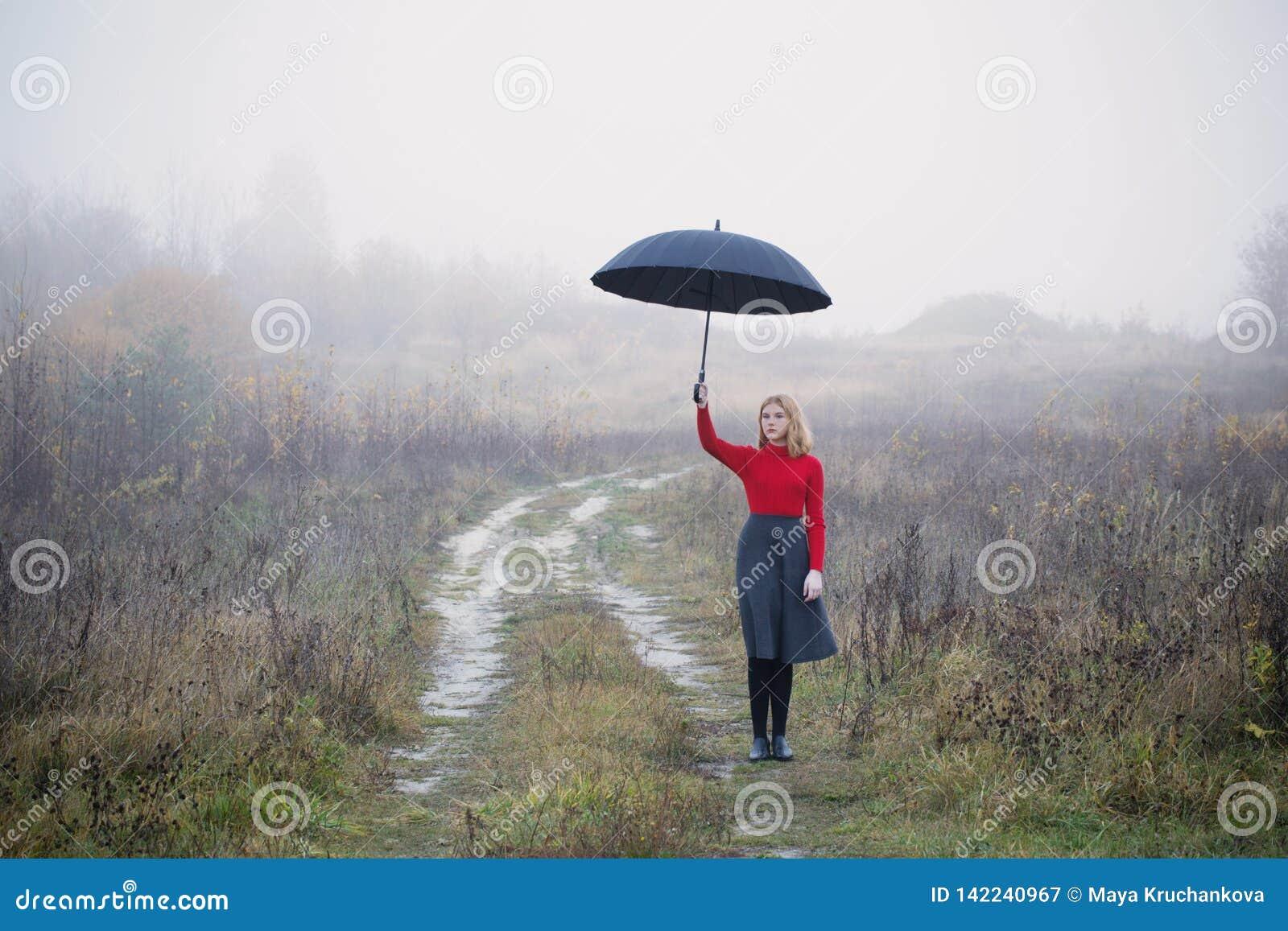 Menina com o guarda-chuva no campo do outono