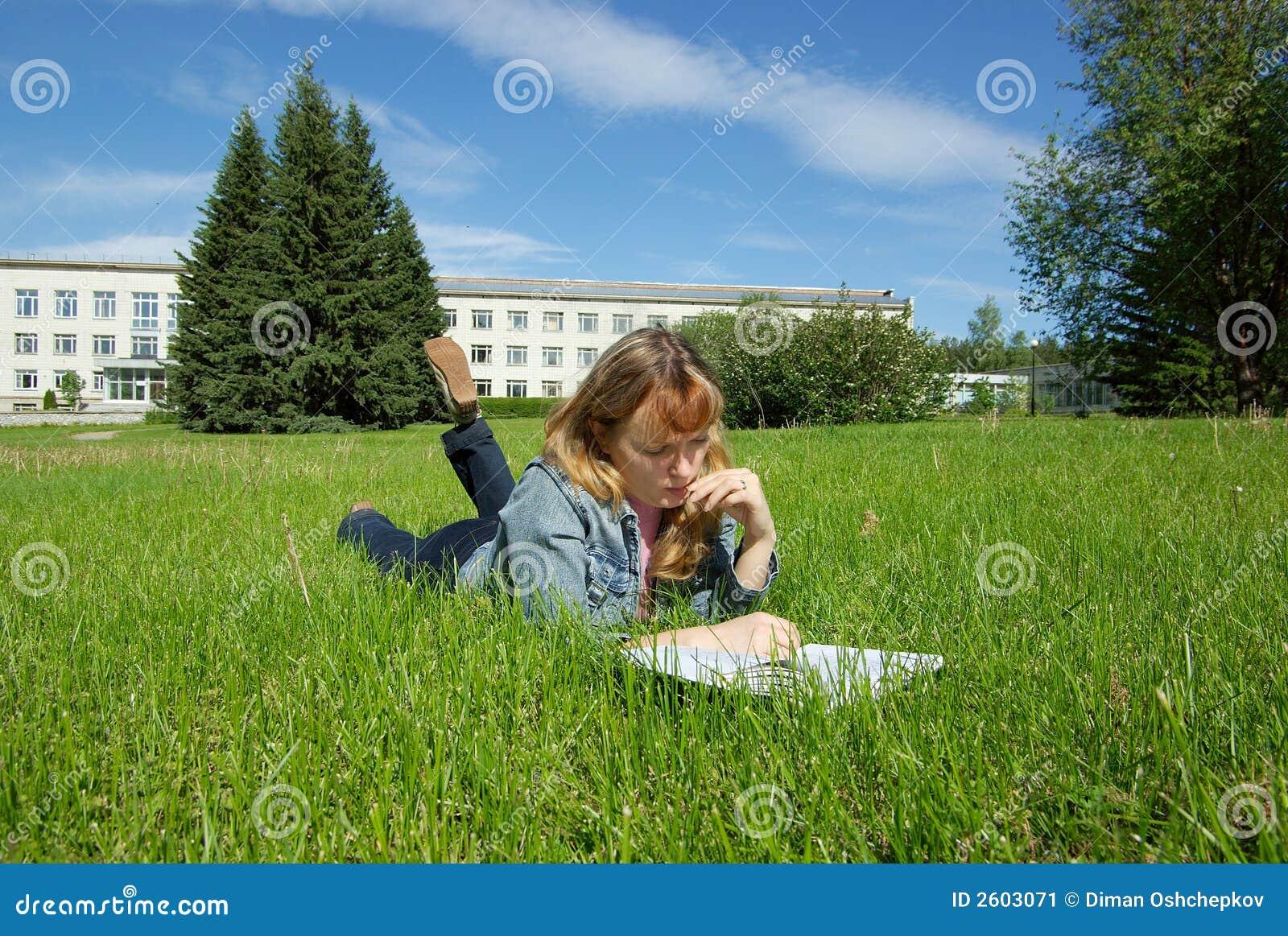 Menina com o livro que encontra-se na grama